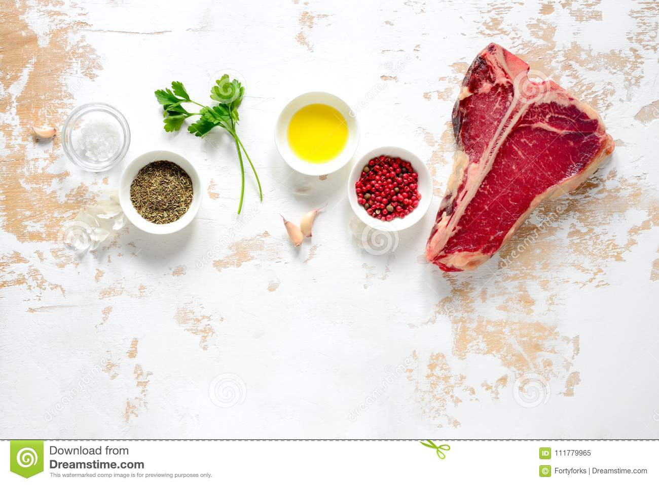Raw t-bone steak and spices on a rustic kitchen table