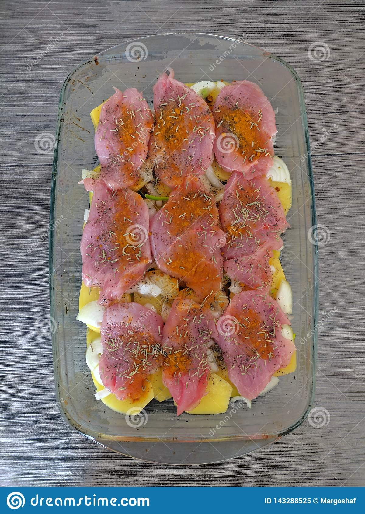 Raw turkey meat marinated with herbs and spices and vegetables - onion, potato in baken roaster before baking. Brown wooden