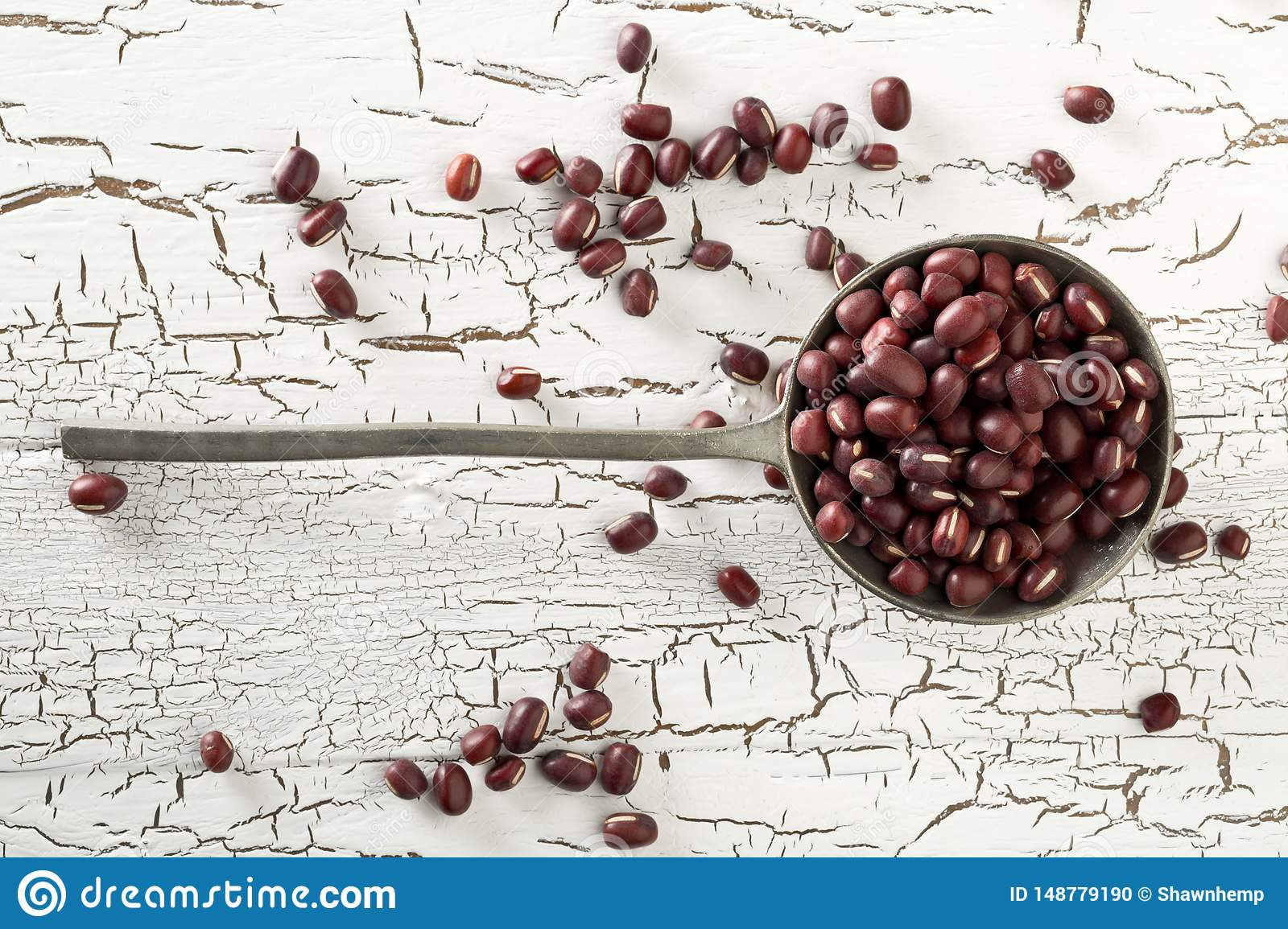 Raw, uncooked, dried adzuki red mung beans in metal spoon on white rustic wood table background top view flat lay