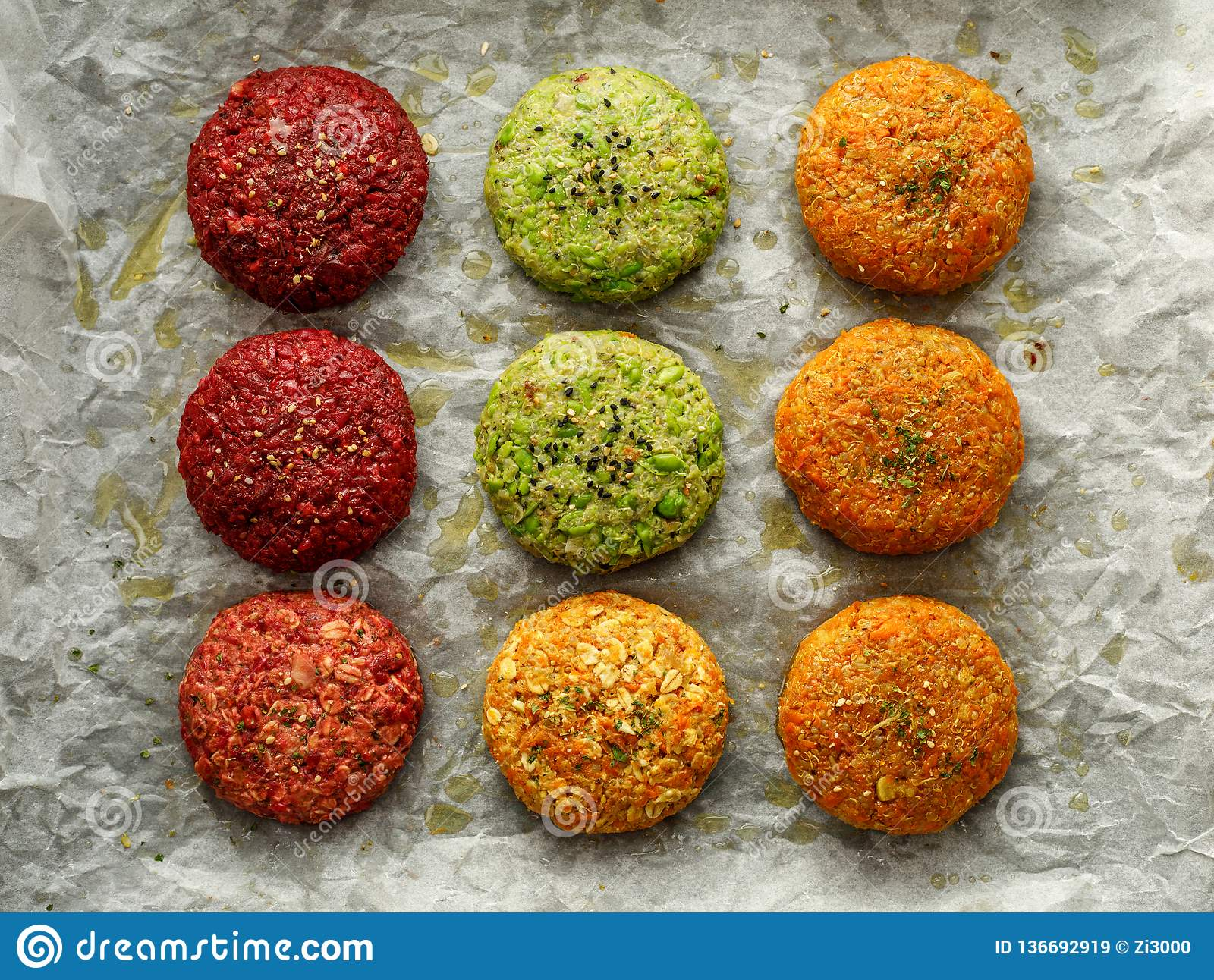 Raw vegan burgers made of beetroot, green peas, carrots, groats and herbs on white parchment prepared for baking, top view.