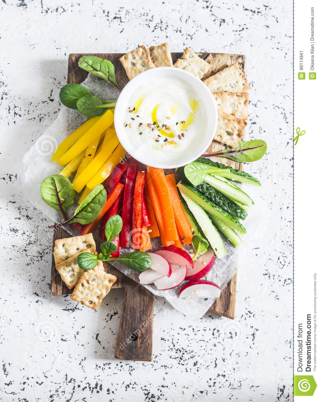 Raw vegetables and yogurt sauce on a wooden cutting board, on a light background, top view. Vegetarian healthy food