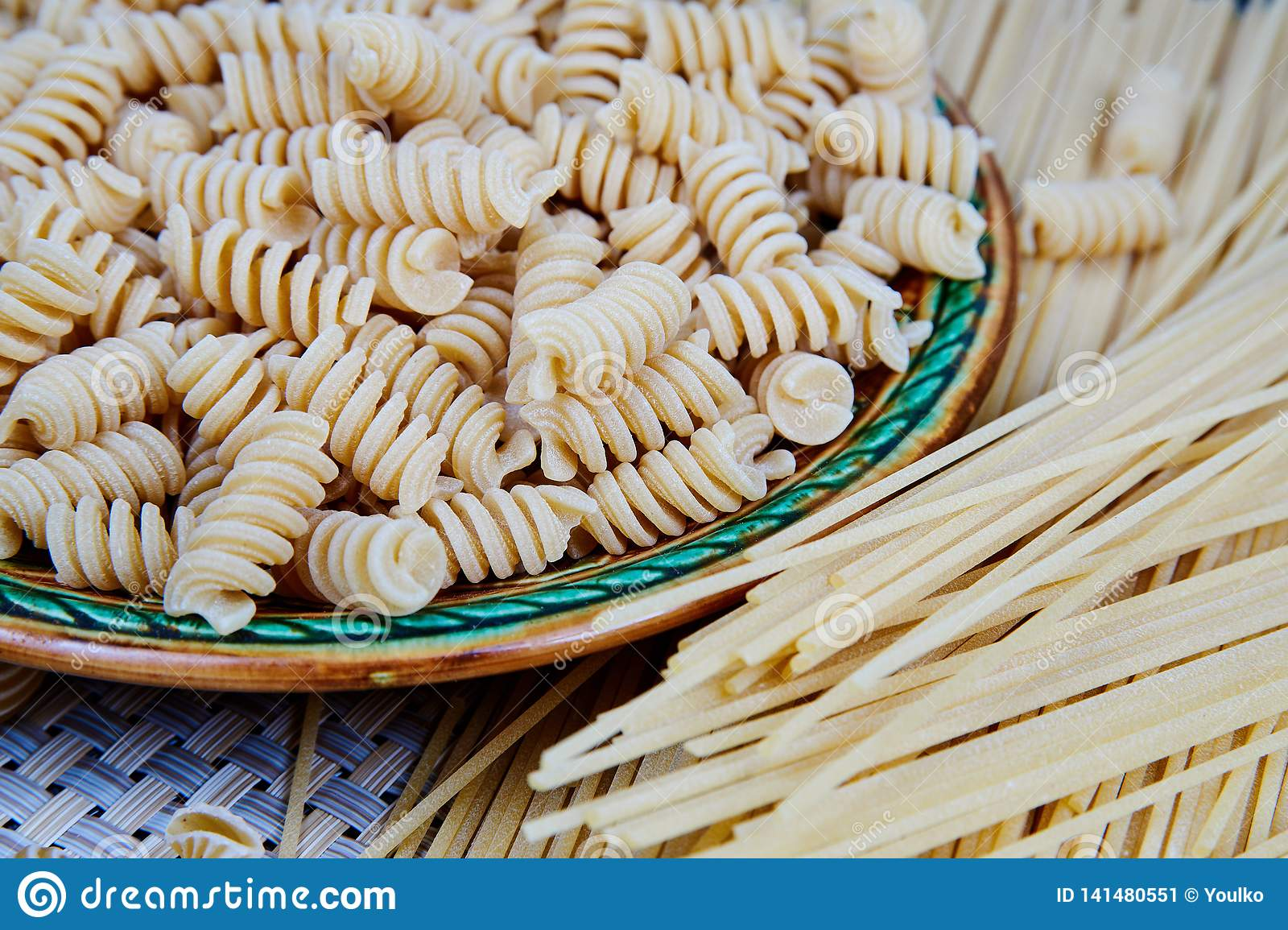 raw whole-grain pasta in a plate on a wicker cloth on the table. top view