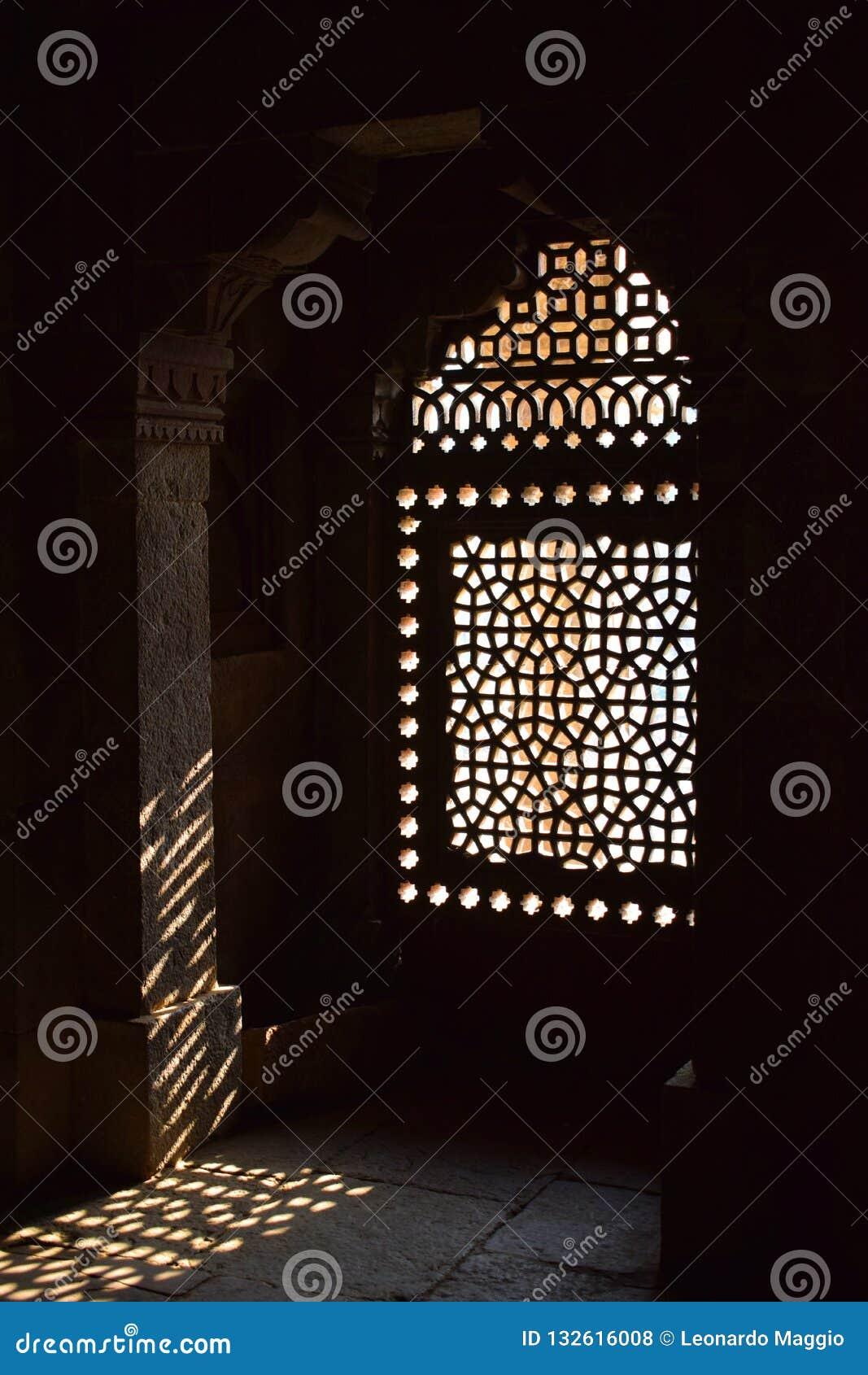 Ray av ljus som skriver in till och med ett fönster av Humayuns gravvalv i Delhi