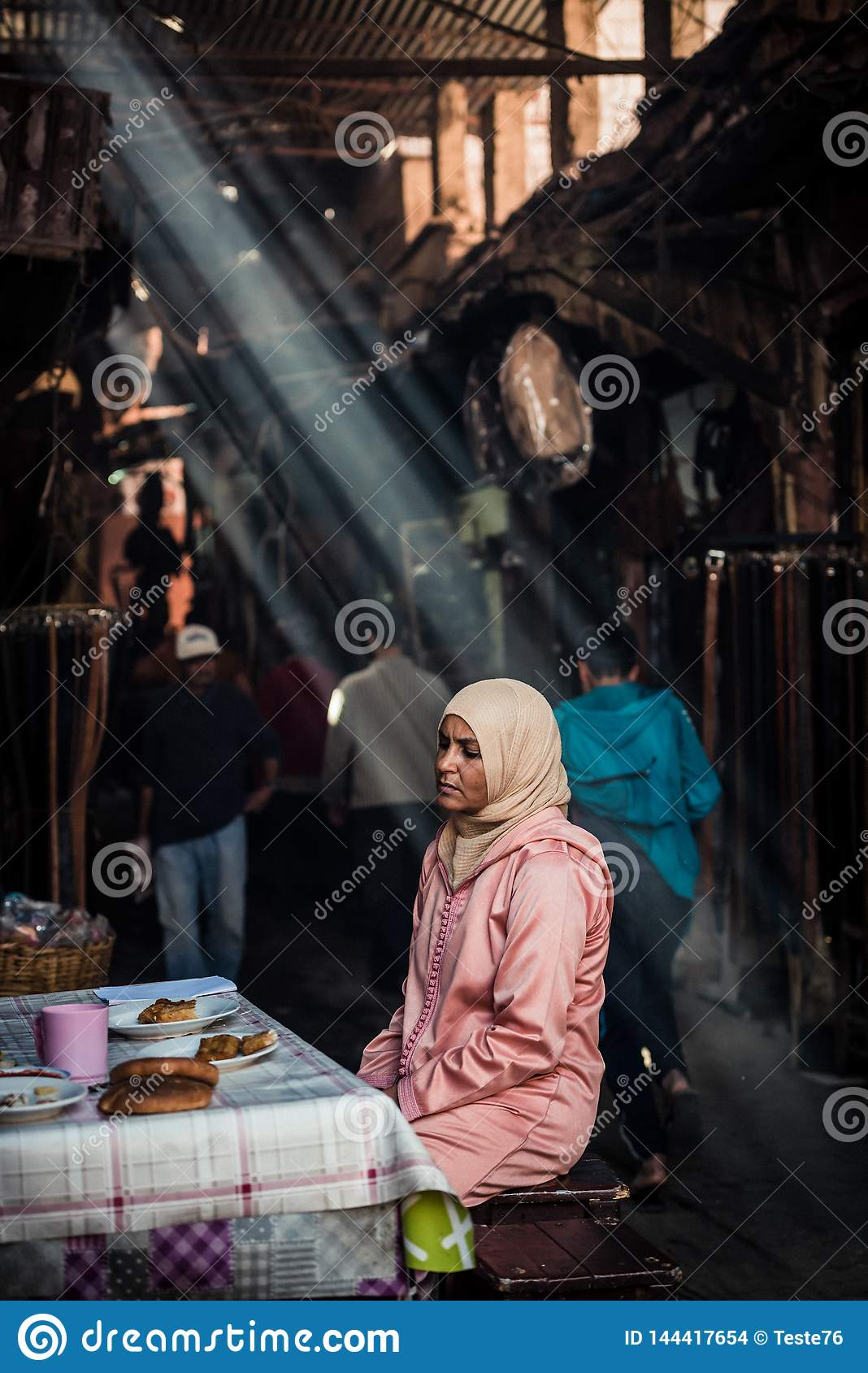 Ray of light. Portrait of an arabian woman sitting at a table as seen in Marrakesh
