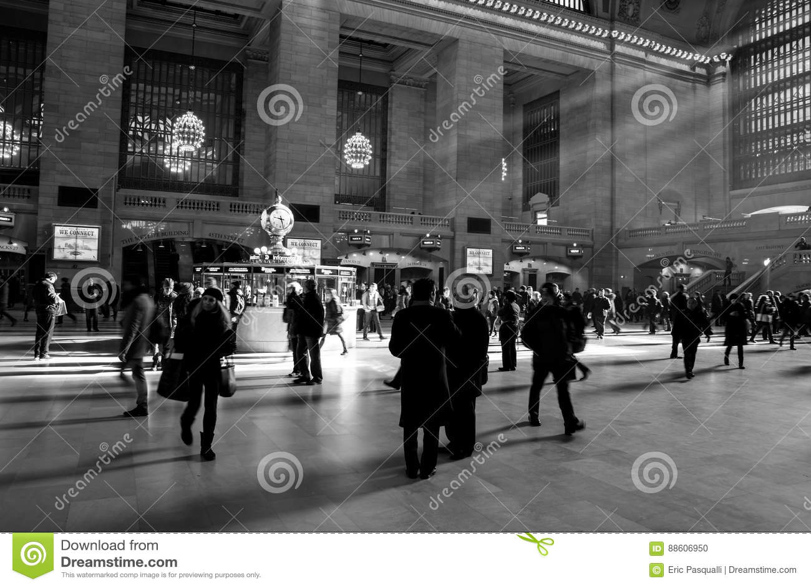 Rayos de la luz del sol dentro de la estación de Grand Central con la gente que camina en el tiempo de la precipitación