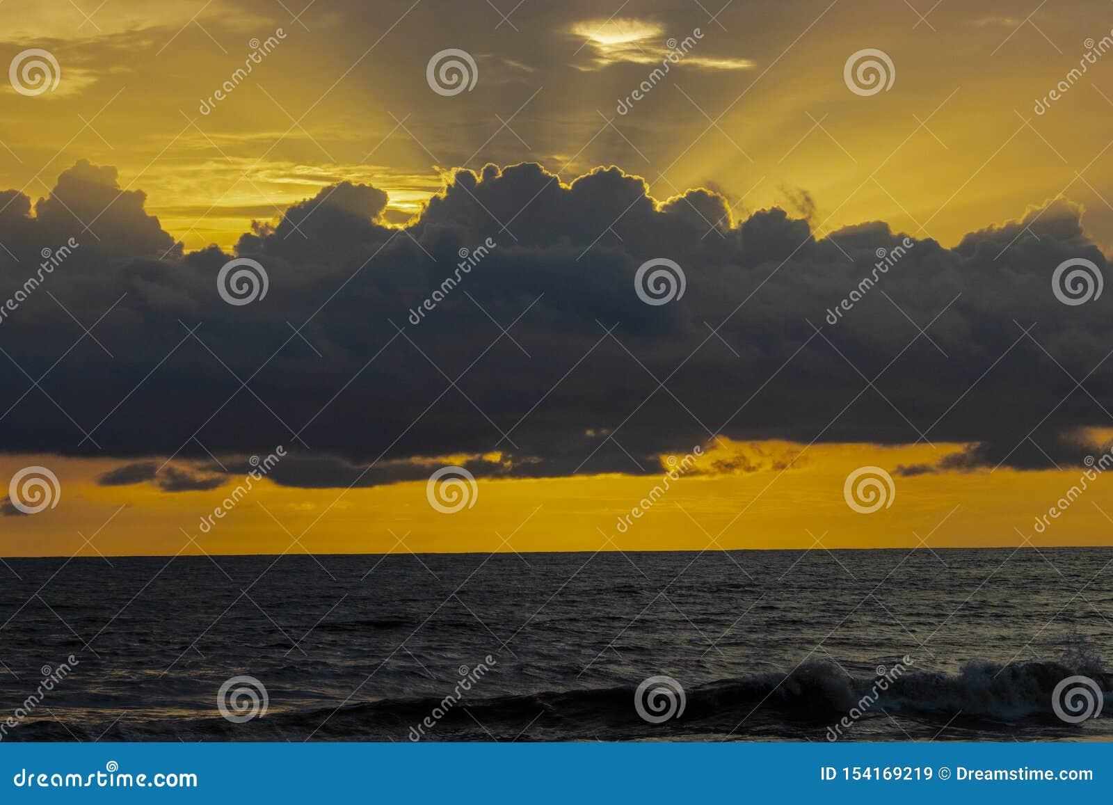 Rayos del sol que vienen del cielo sobre el mar