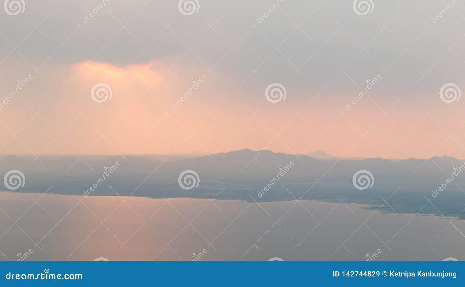 Rayos hermosos de Sun a través de las nubes sobre las montañas y la presa