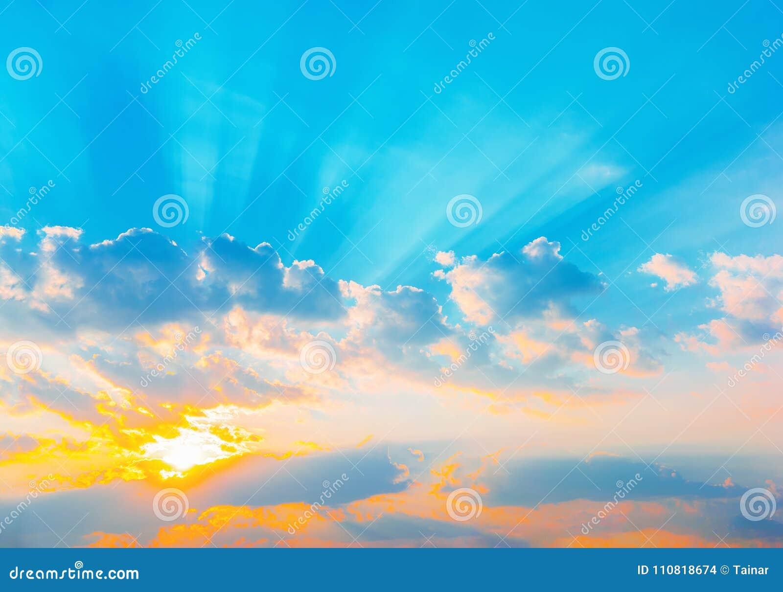Rays dramatisk blå himmel för soluppgång med den orange solen avbrott till och med molnen mot bakgrund field blåa oklarheter för