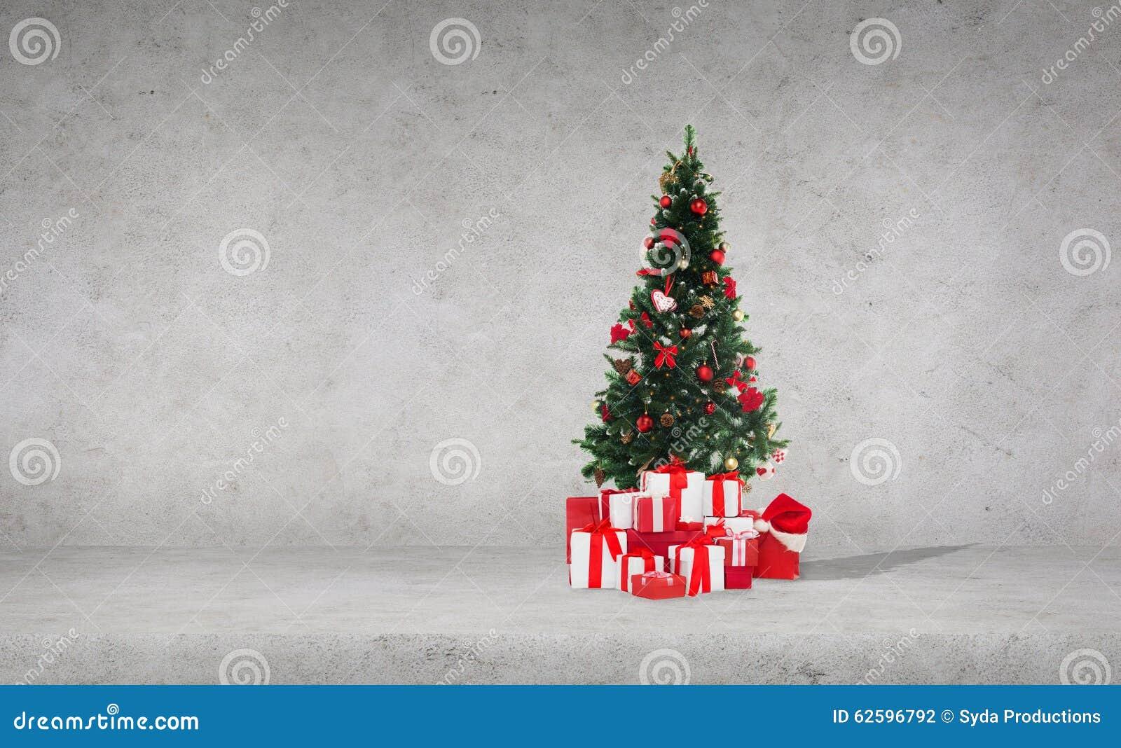 Rbol de navidad con los regalos sobre el muro de cemento - Arbol de navidad con regalos ...