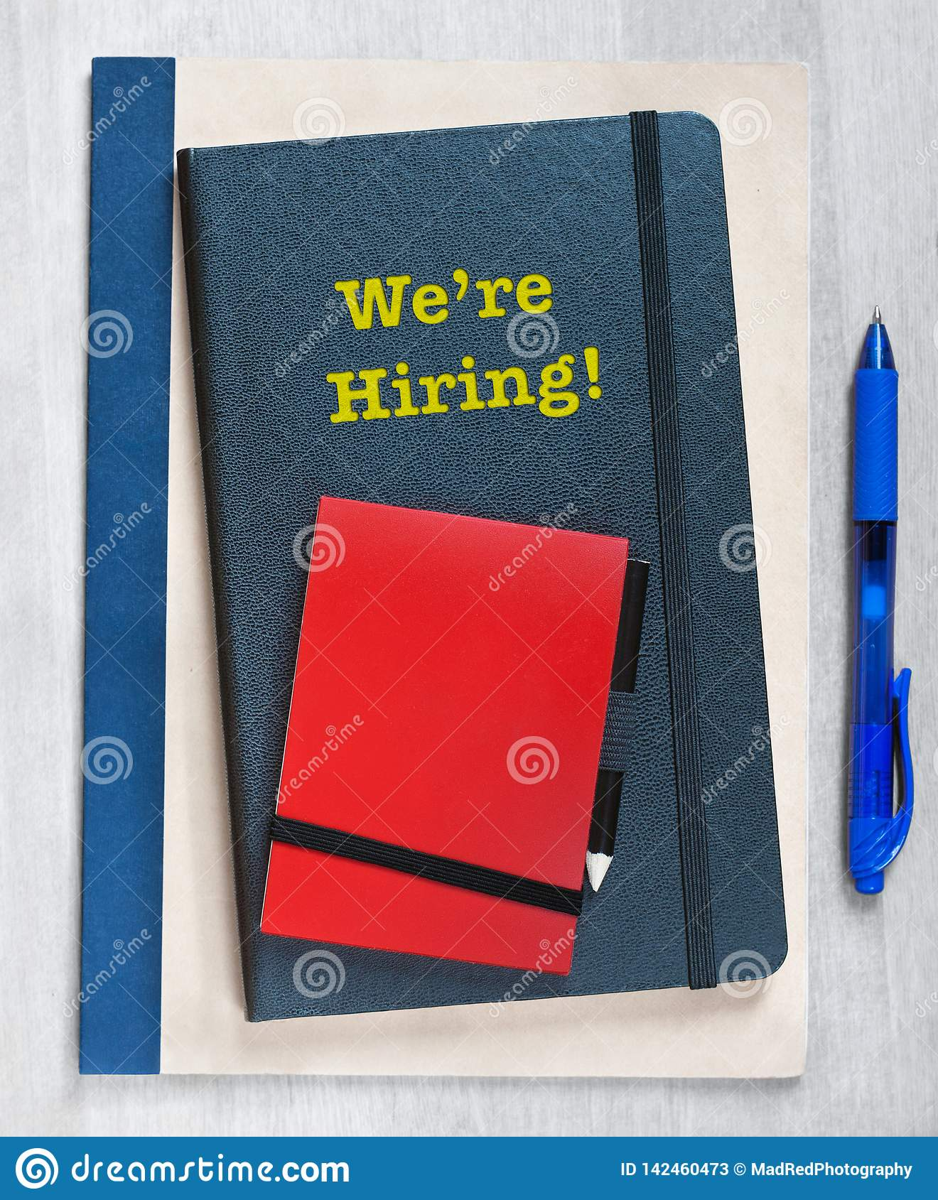 We`re Hiring! Text written on a pile of notebooks, next to a blue pen on a wooden background