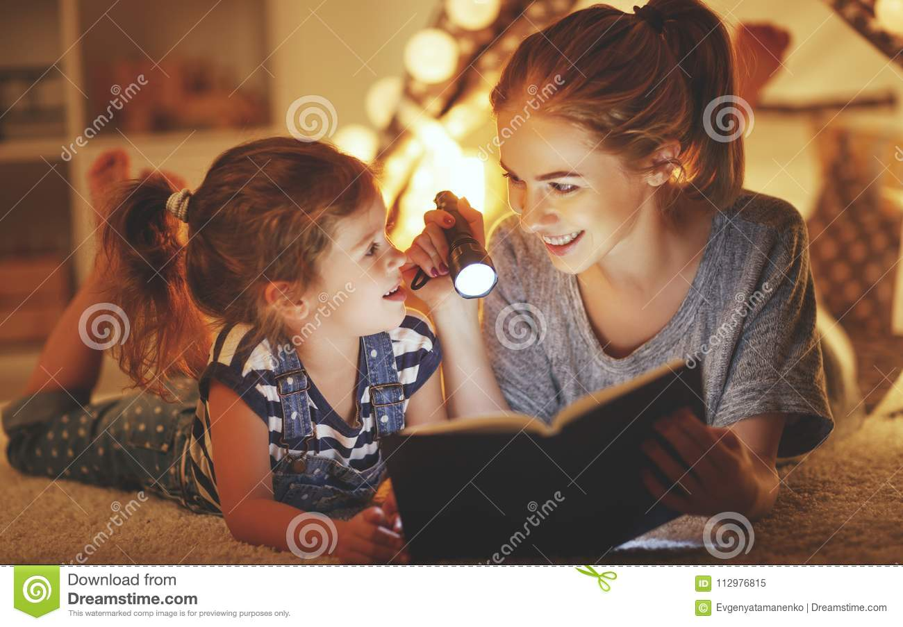 Mother and child daughter reading a book and a flashlight before