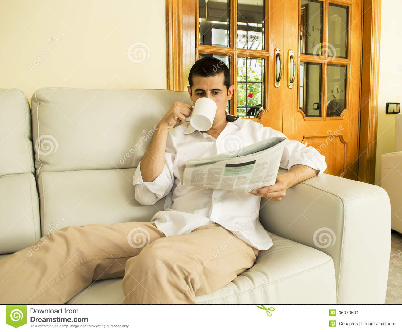 Man drinking coffee and reading newspaper on the sofa.