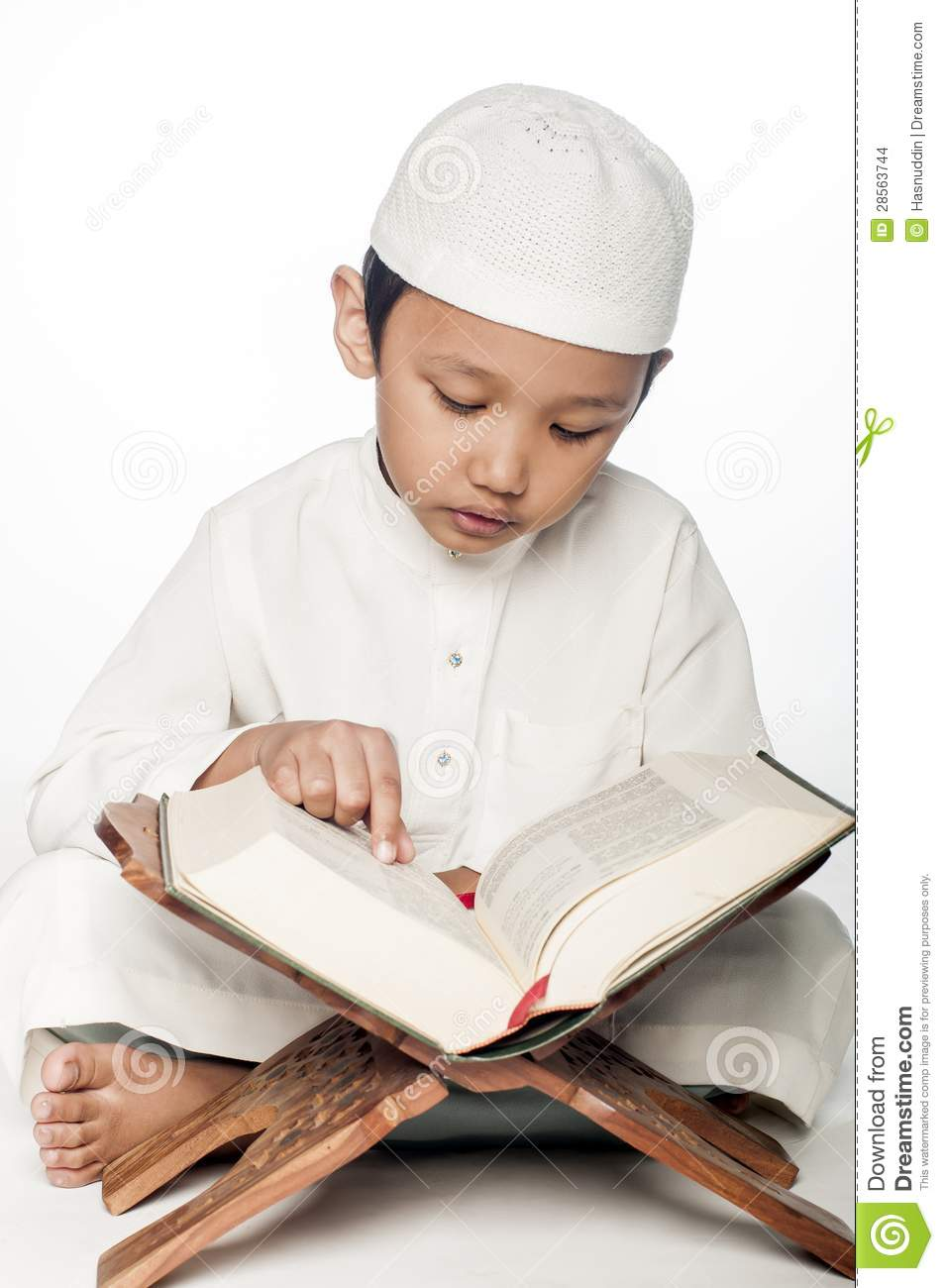 little muslim boy wearing islamic attire reading the holy Quran.