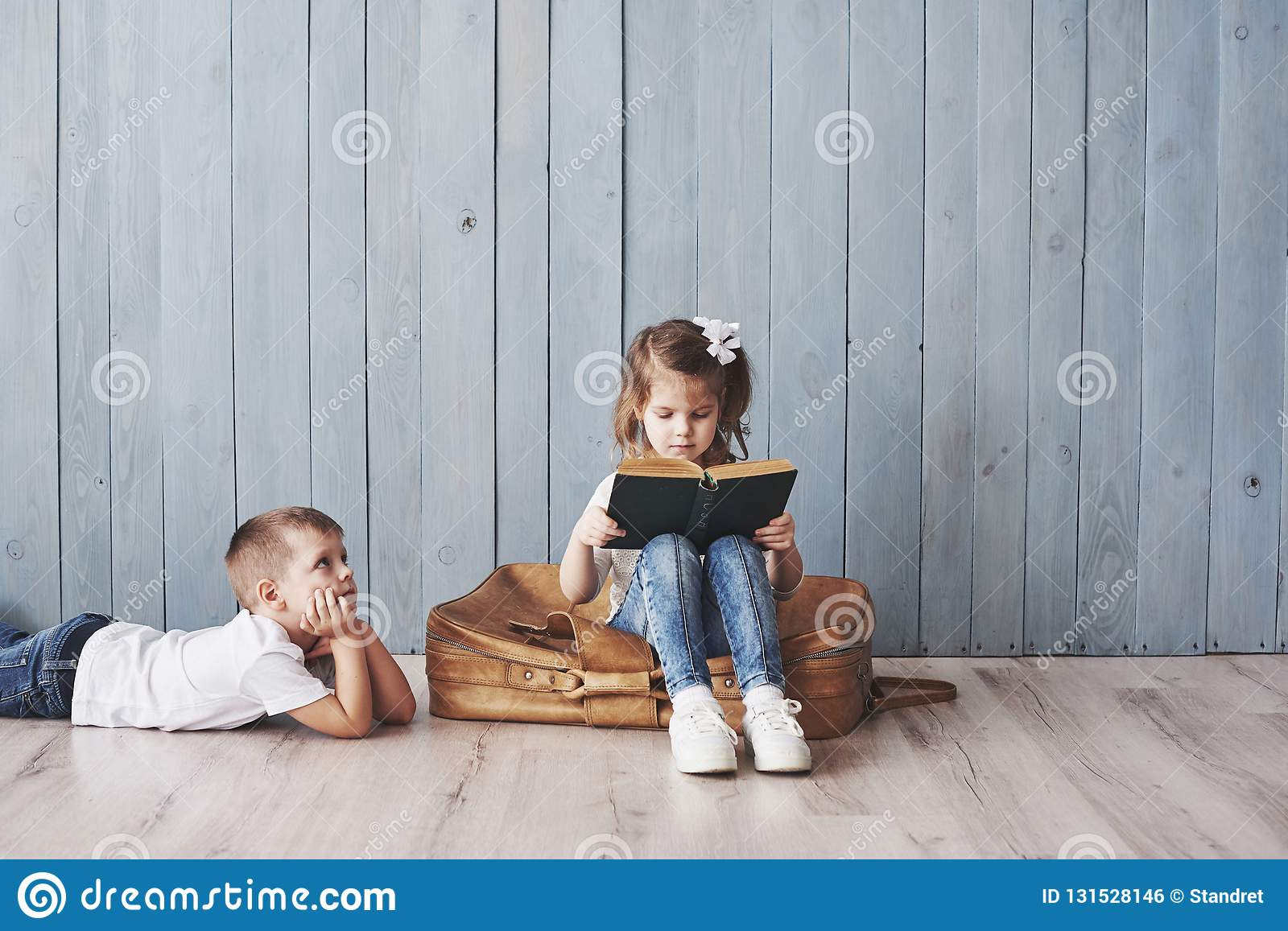 Ready to big travel. Happy little girl and boy reading interesting book carrying a big briefcase and smiling. Travel