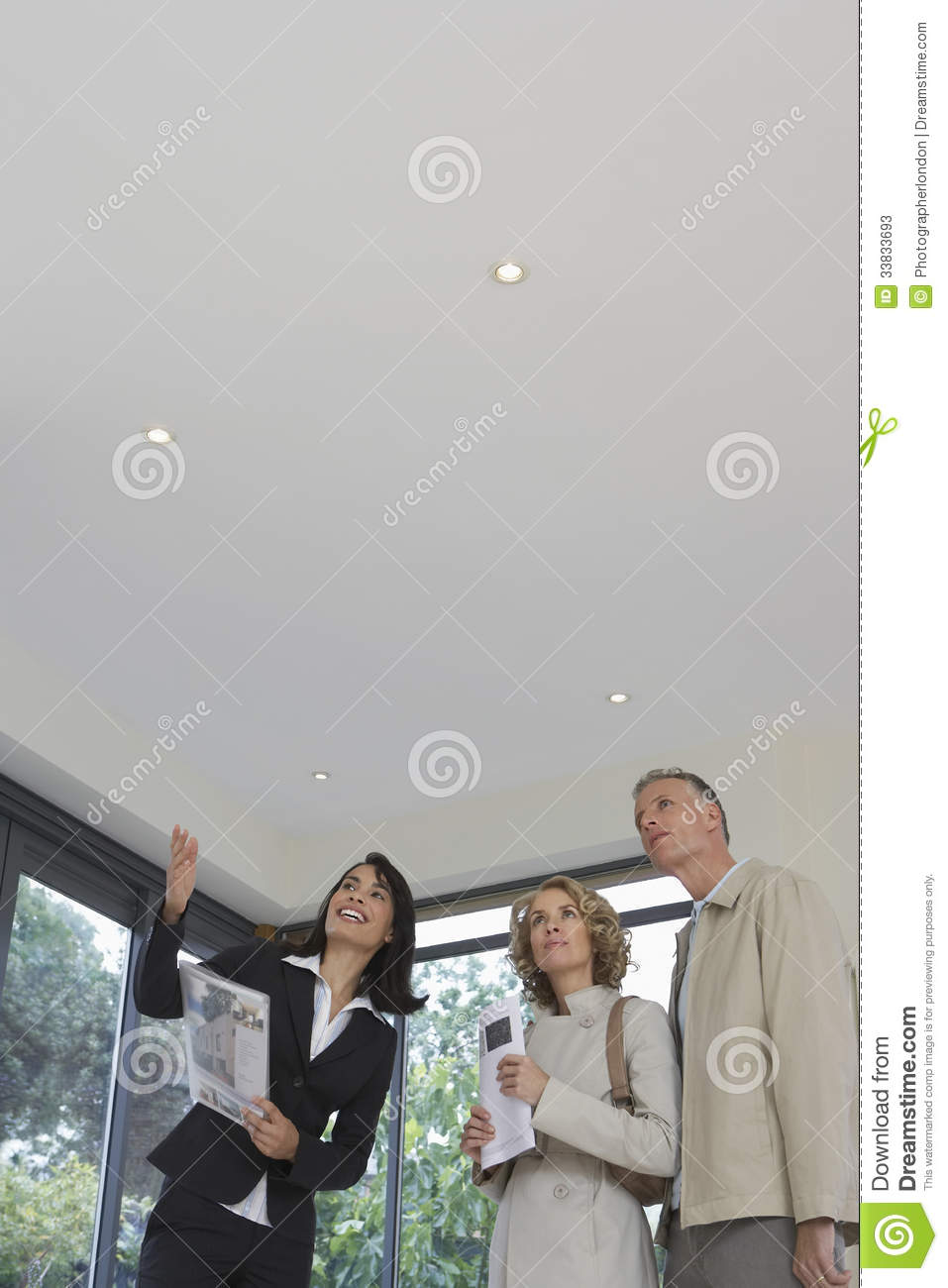 Real Estate Agent And Couple Observing New Property