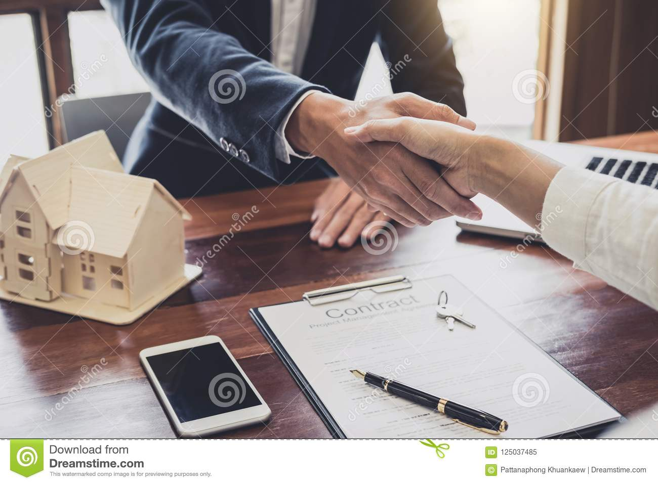 Real estate agent and customers shaking hands together celebrati