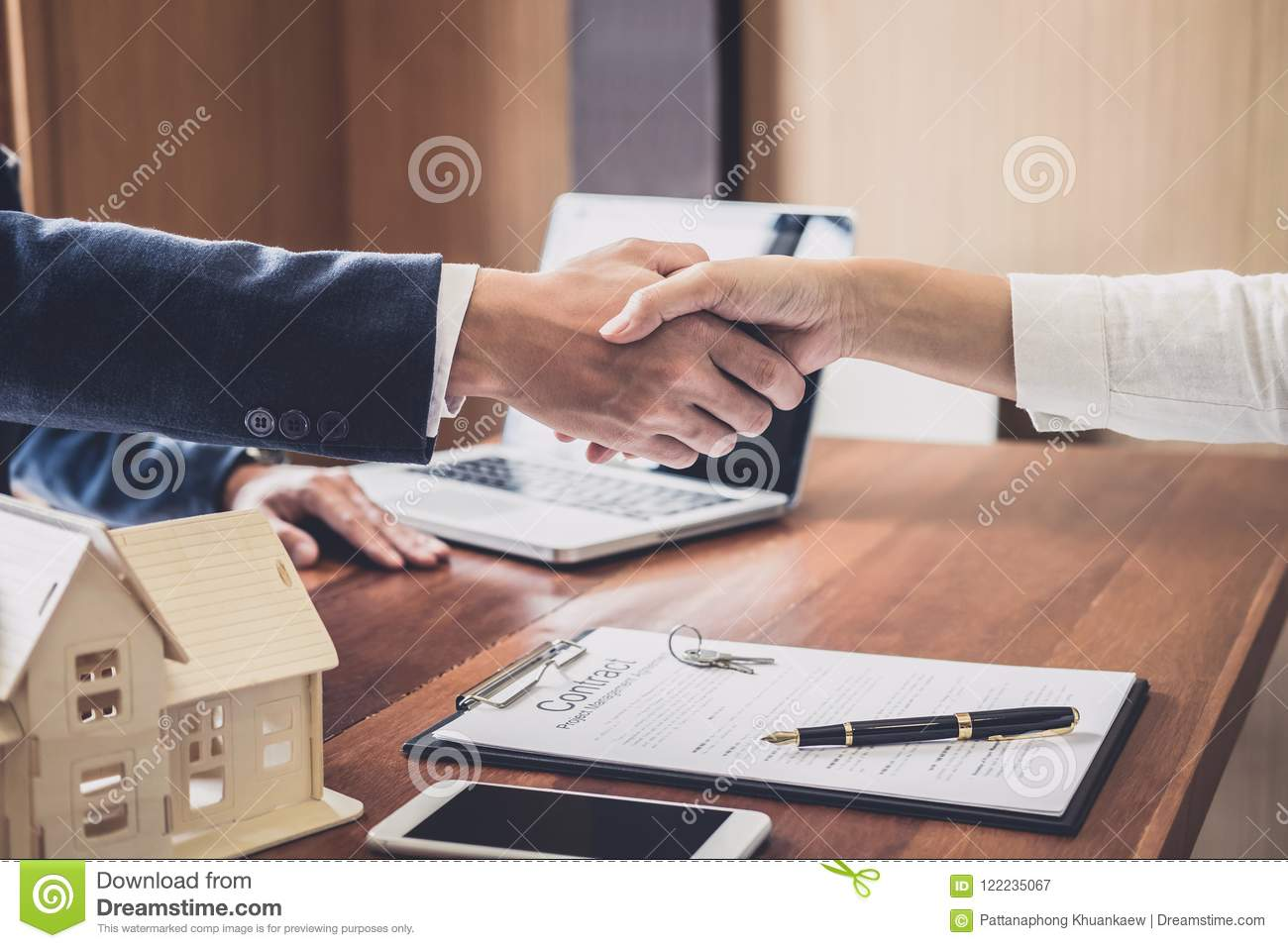 Real estate agent and customers shaking hands together celebrating finished contract after about home insurance and investment lo