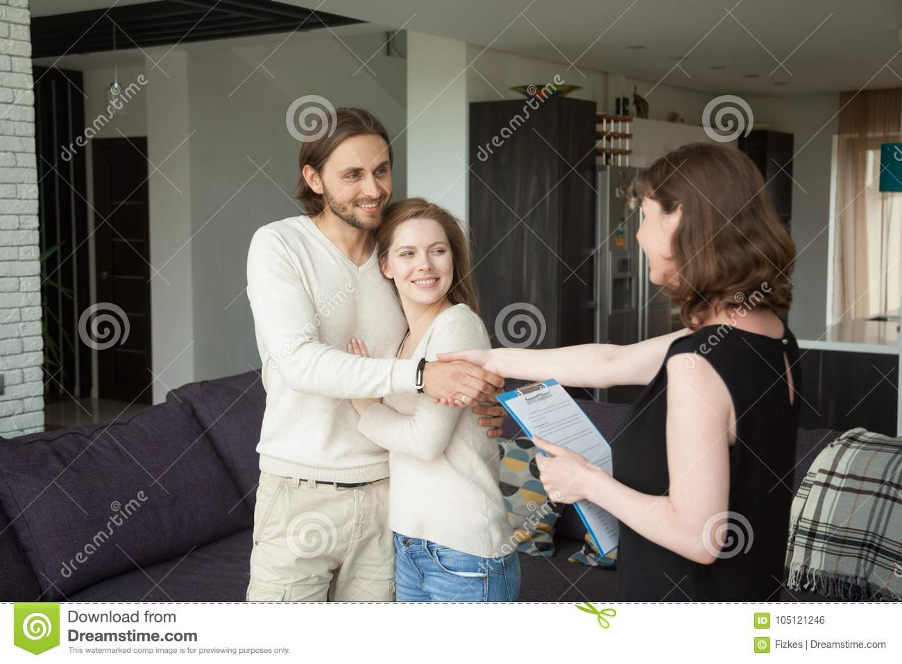 Real estate agent shaking hands couple clients in rental house