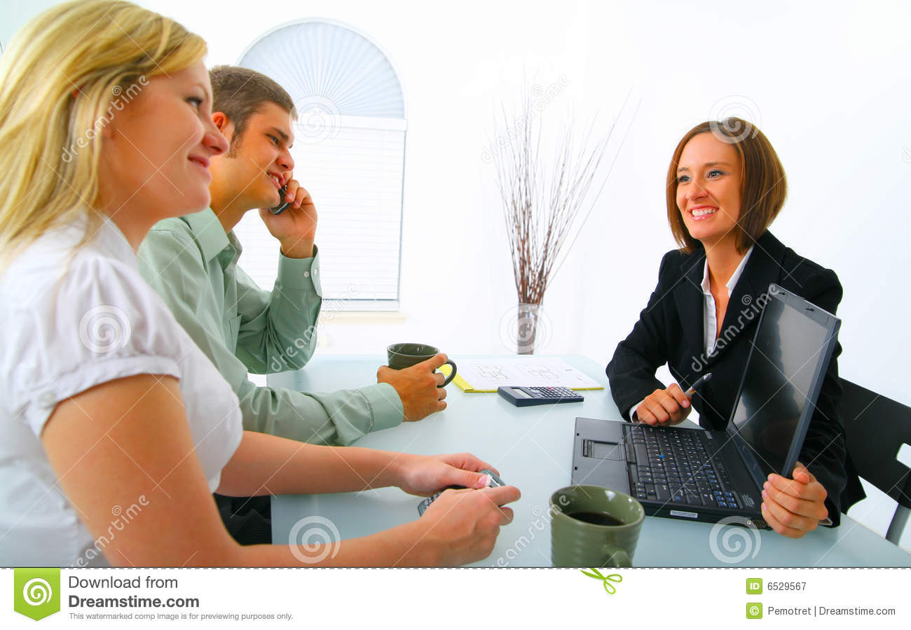 Real Estate Broker Showing Laptop To Clients