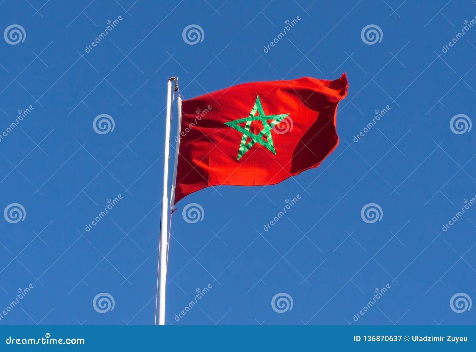 Real flaga Morocco na niebieskiego nieba tle