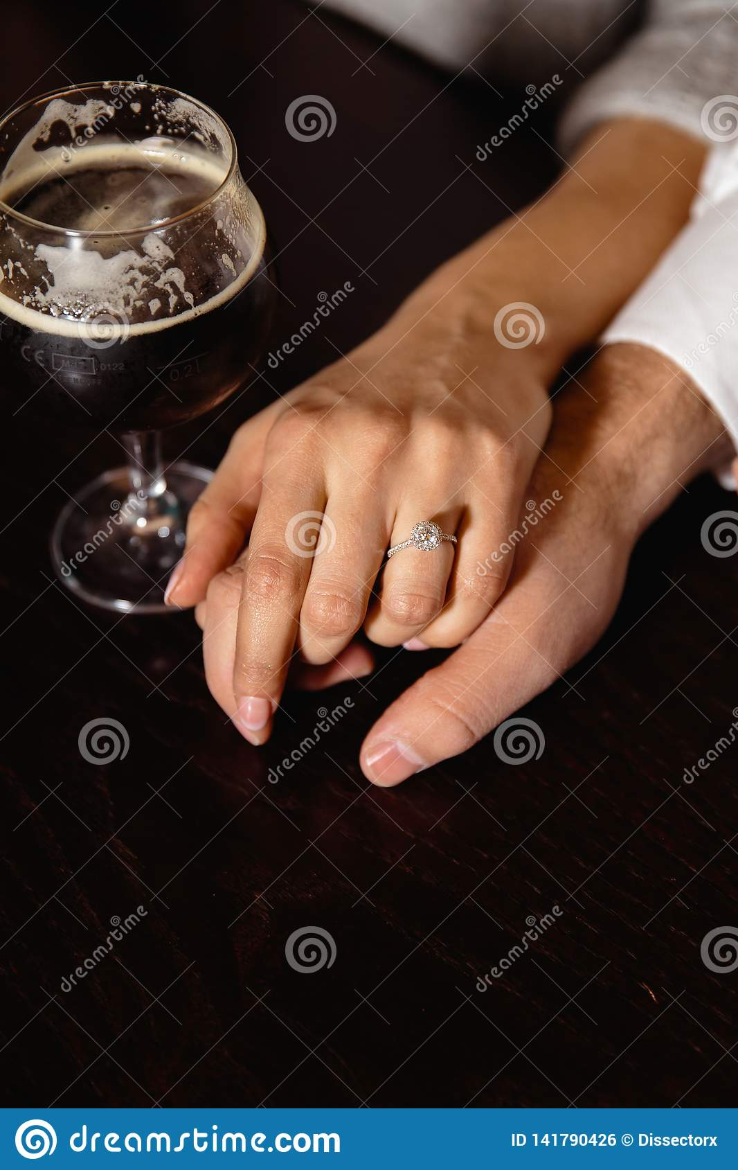 Real life proposal: Couple holding hands in a pub with a glass of beer to their side