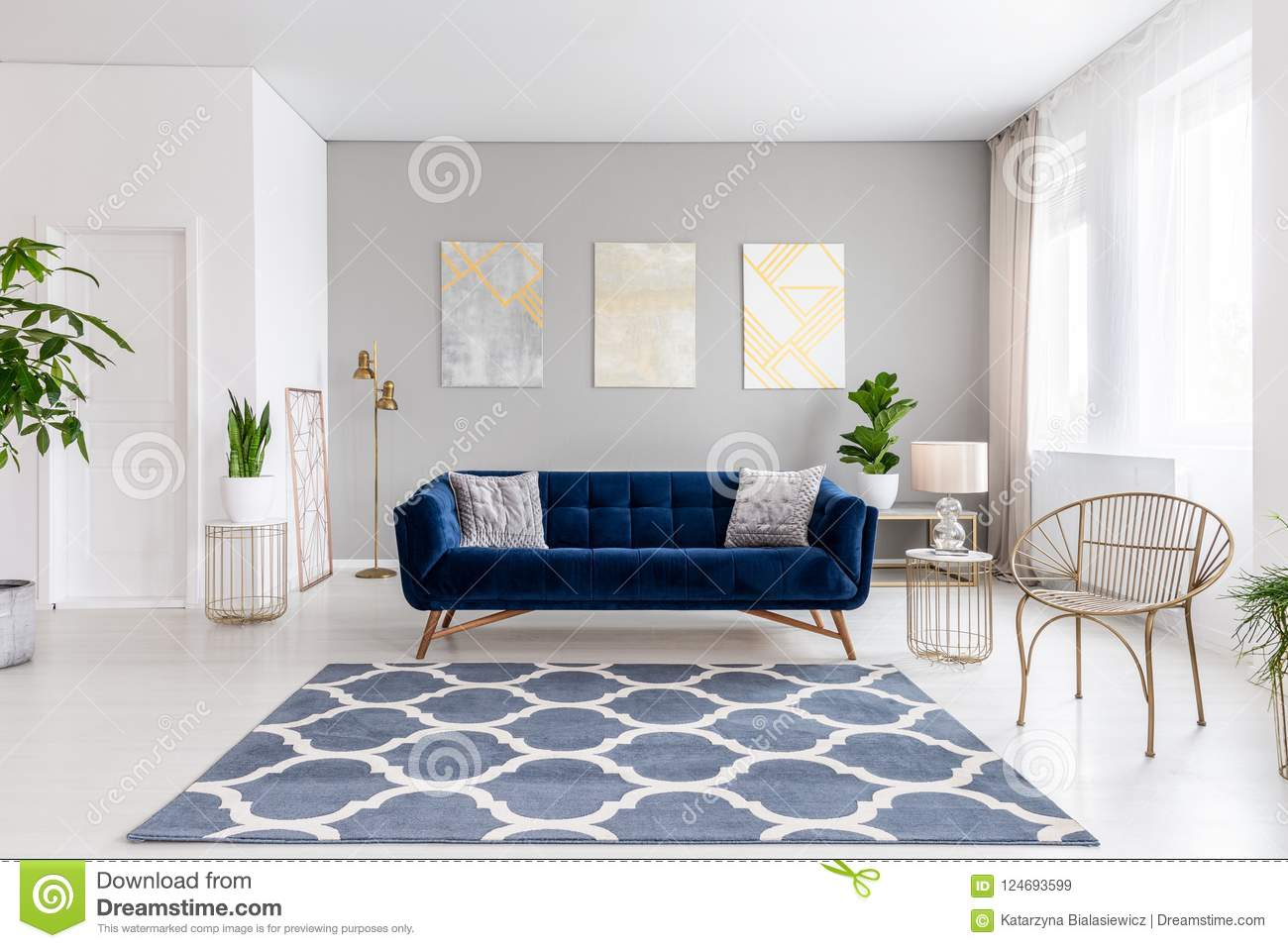 real photo of bright living room interior with royal blue couch