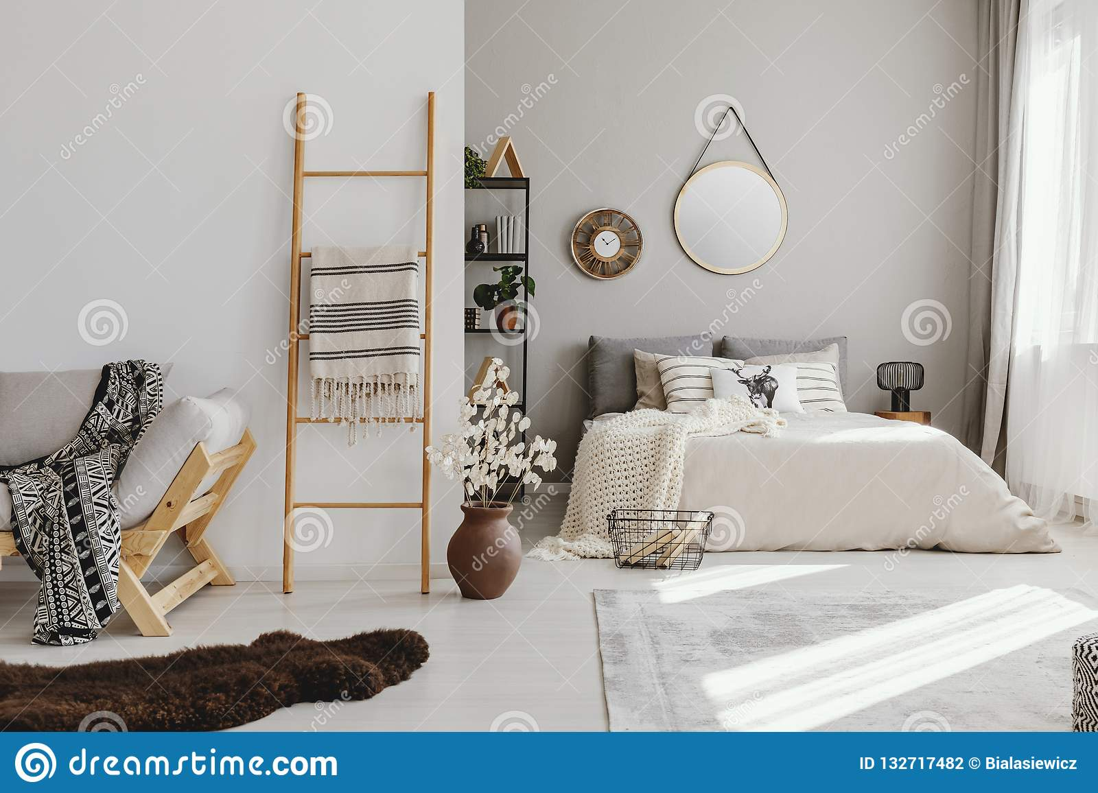 open space bedroom interior with window with curtains, mirror and clock on the wall, ladder with blanket,