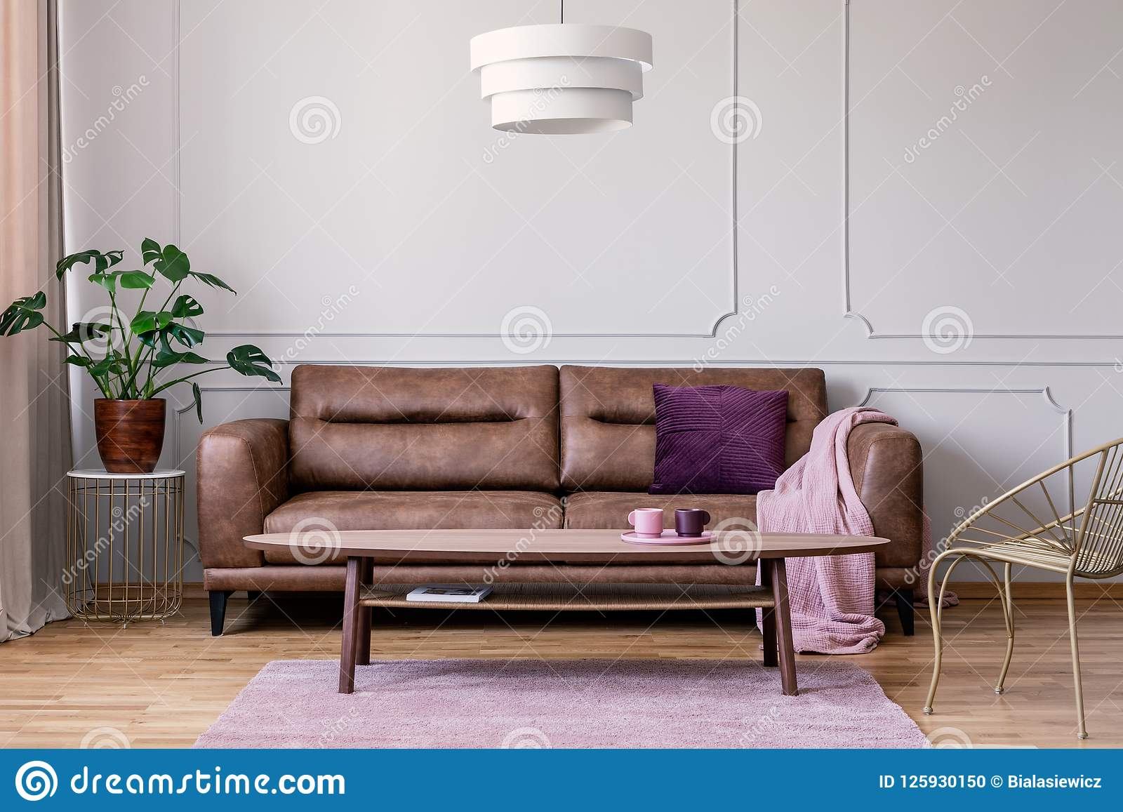 Real photo of brown leather sofa with violet cushion and pastel pink blanket standing in light grey sitting room interior with Mon