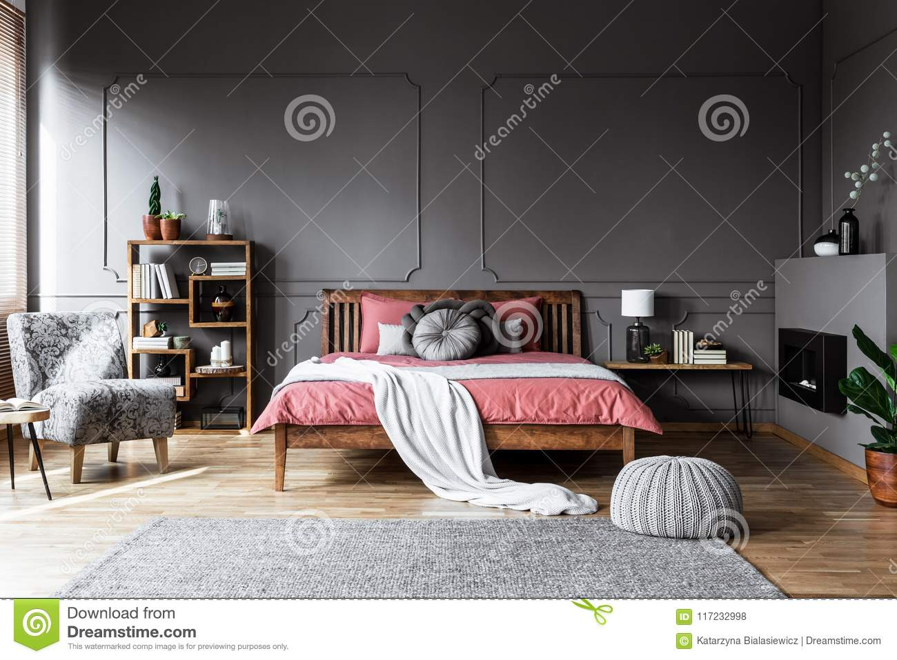Real photo of a cozy bedroom interior with wooden bed in the mid