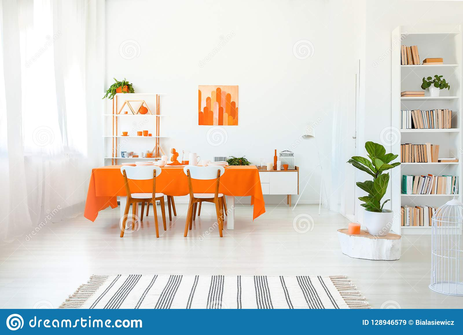 Dining room in vivid color. Orange tablecloth on table with white chairs