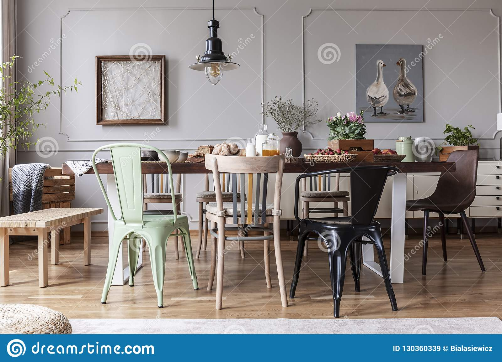 Real Photo Of An Eclectic Dining Room Interior With Various Chairs At The Table Lamp And Painting With Ducks Stock Image Image Of Molding Interior 130360339
