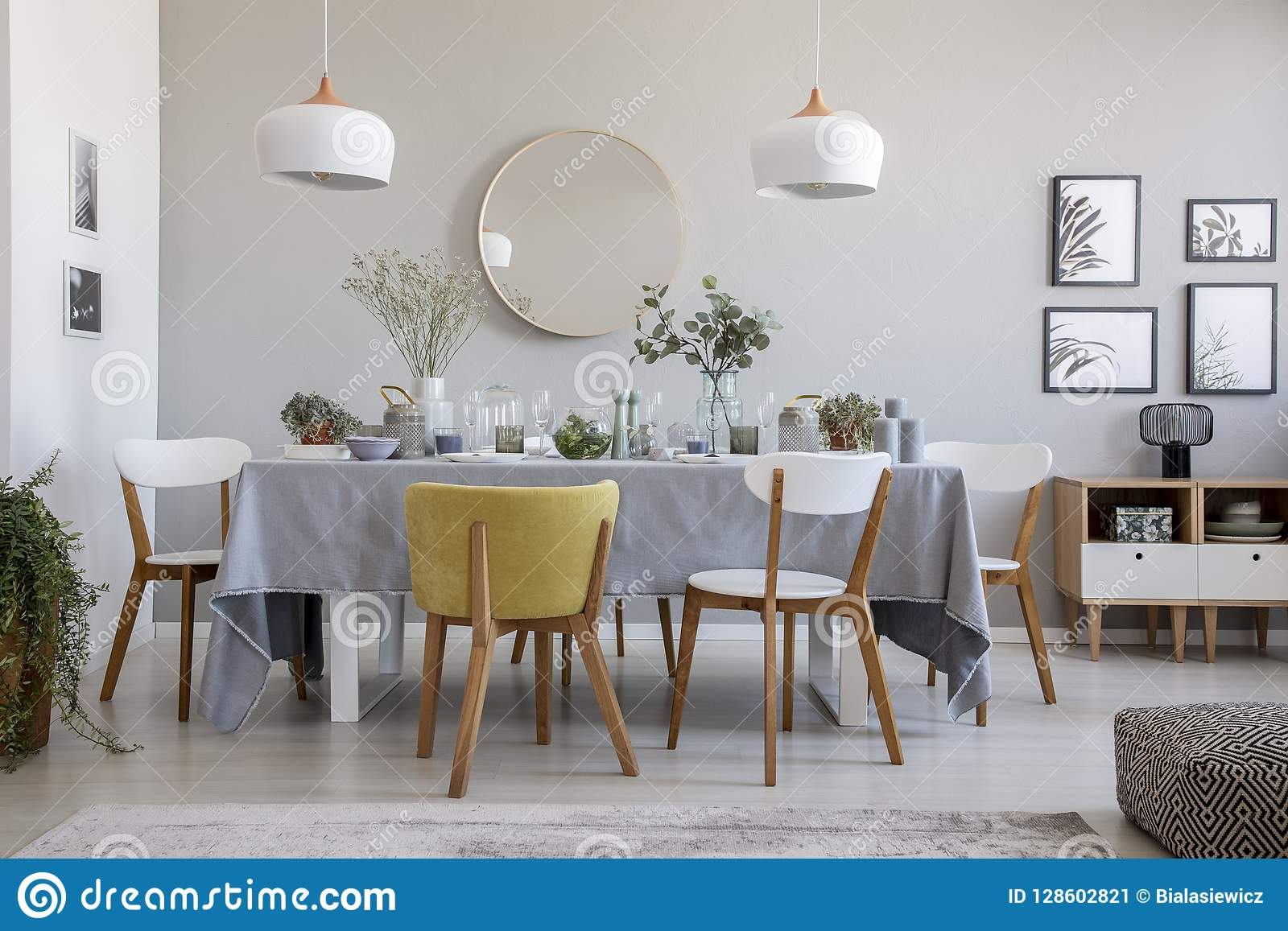 Elegant dining room interior with a laid table, chairs, mirror on a wall and lamps