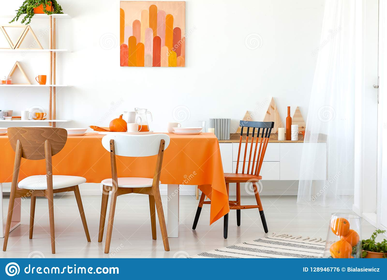 Kitchen Table Covered With Orange Tablecloth And White