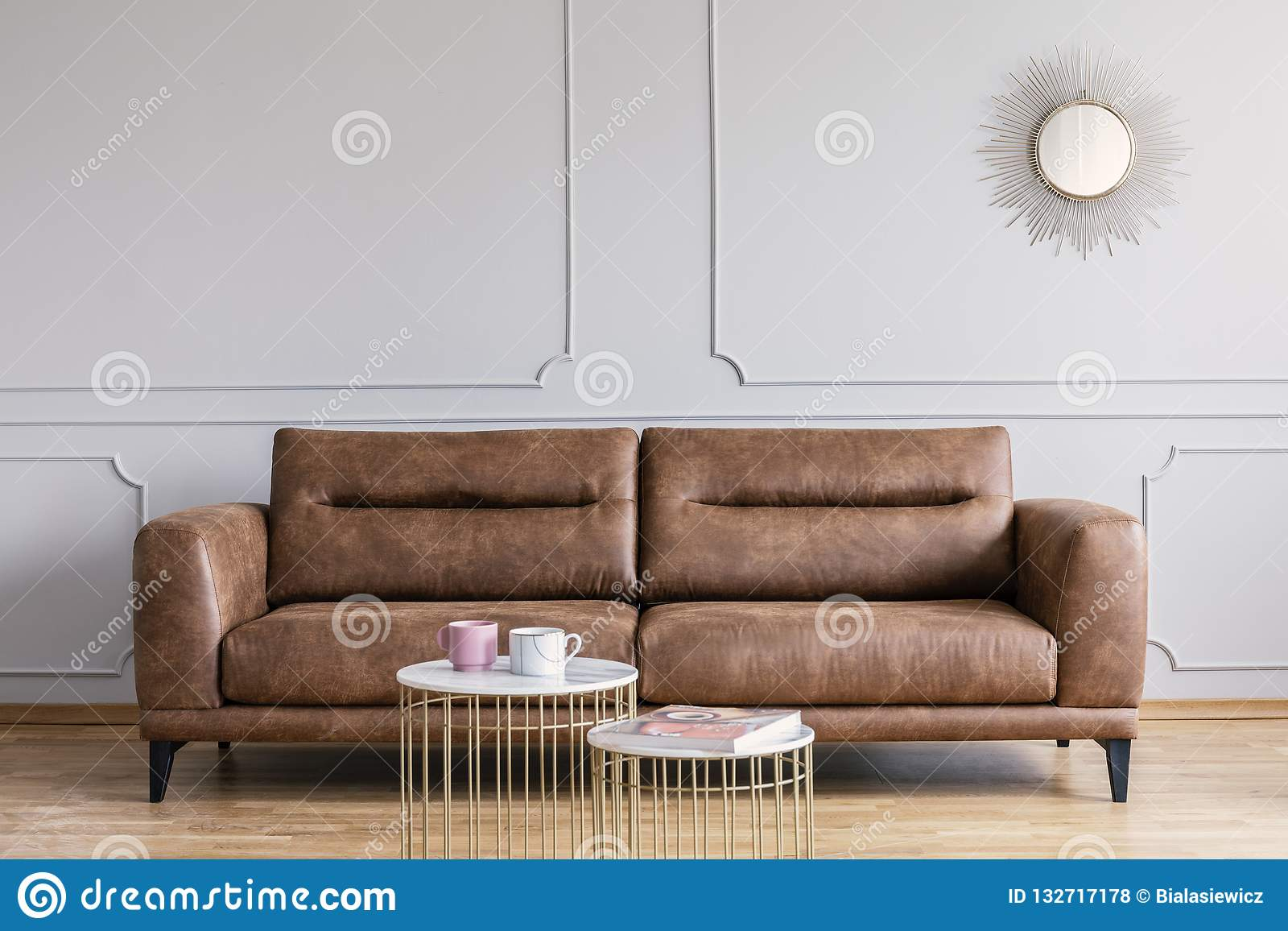 Leather sofa, coffee tables and mirror in a living room interior