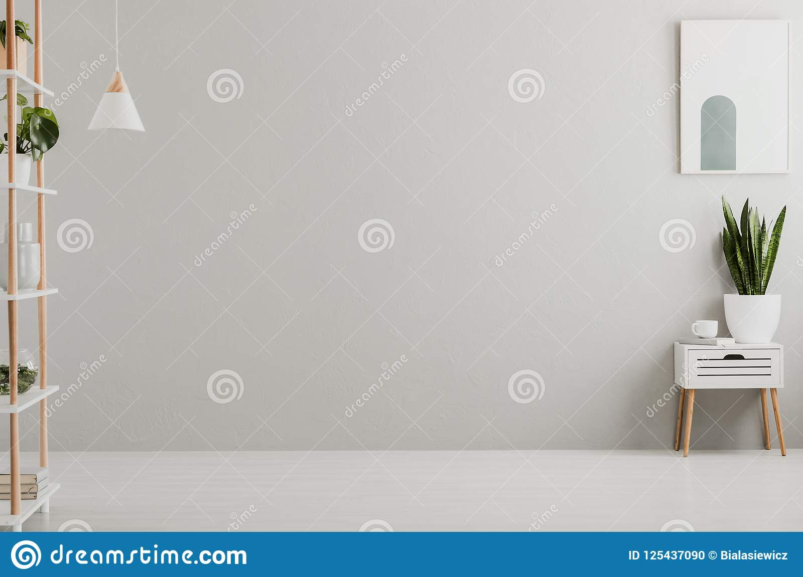 Real photo of light grey living room interior with fresh plants, book and tea cup on cupboard and simple poster on the wall, Place