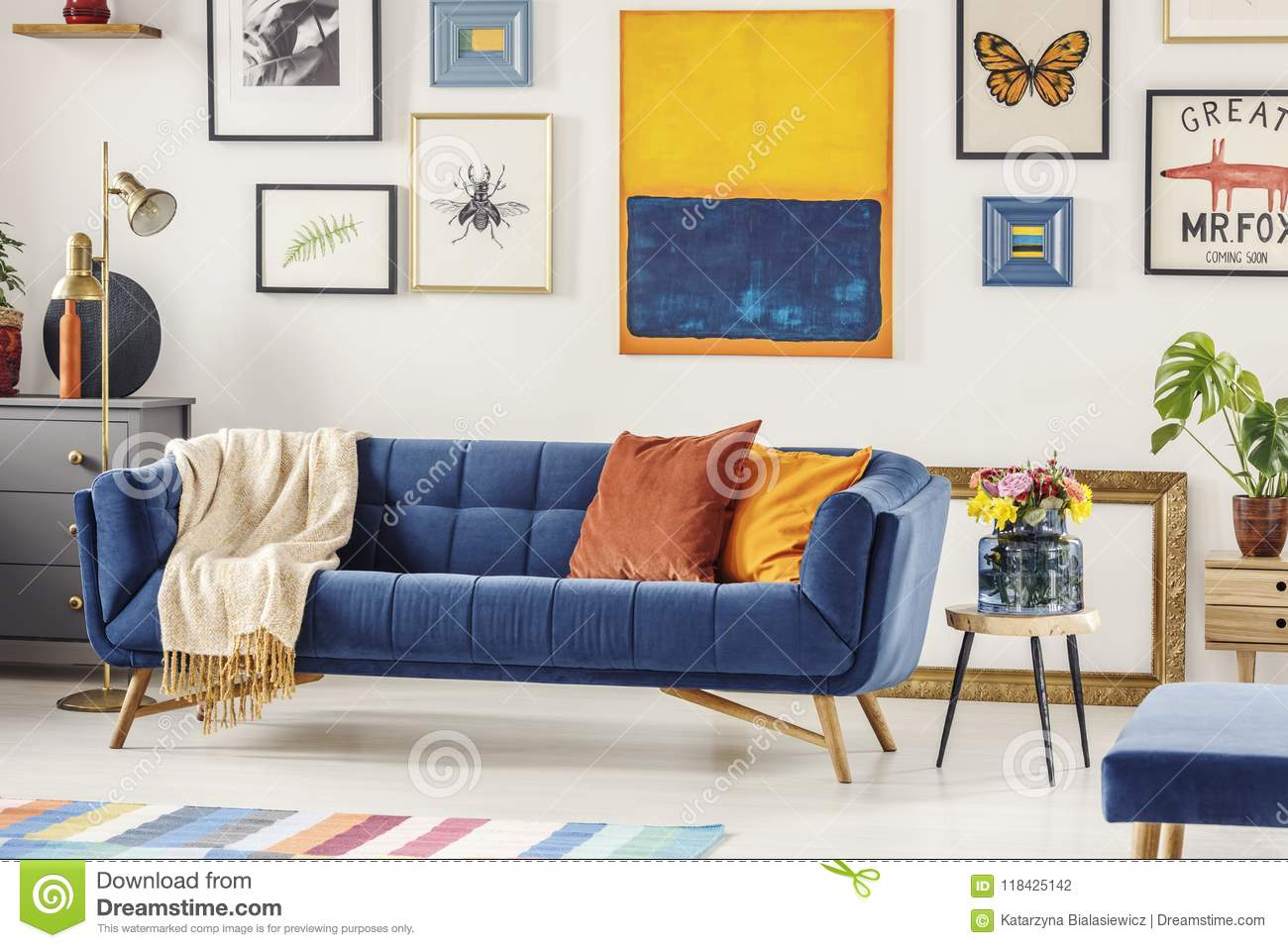Real Photo Of A Navy Blue Couch With A Blanket And Orange ...