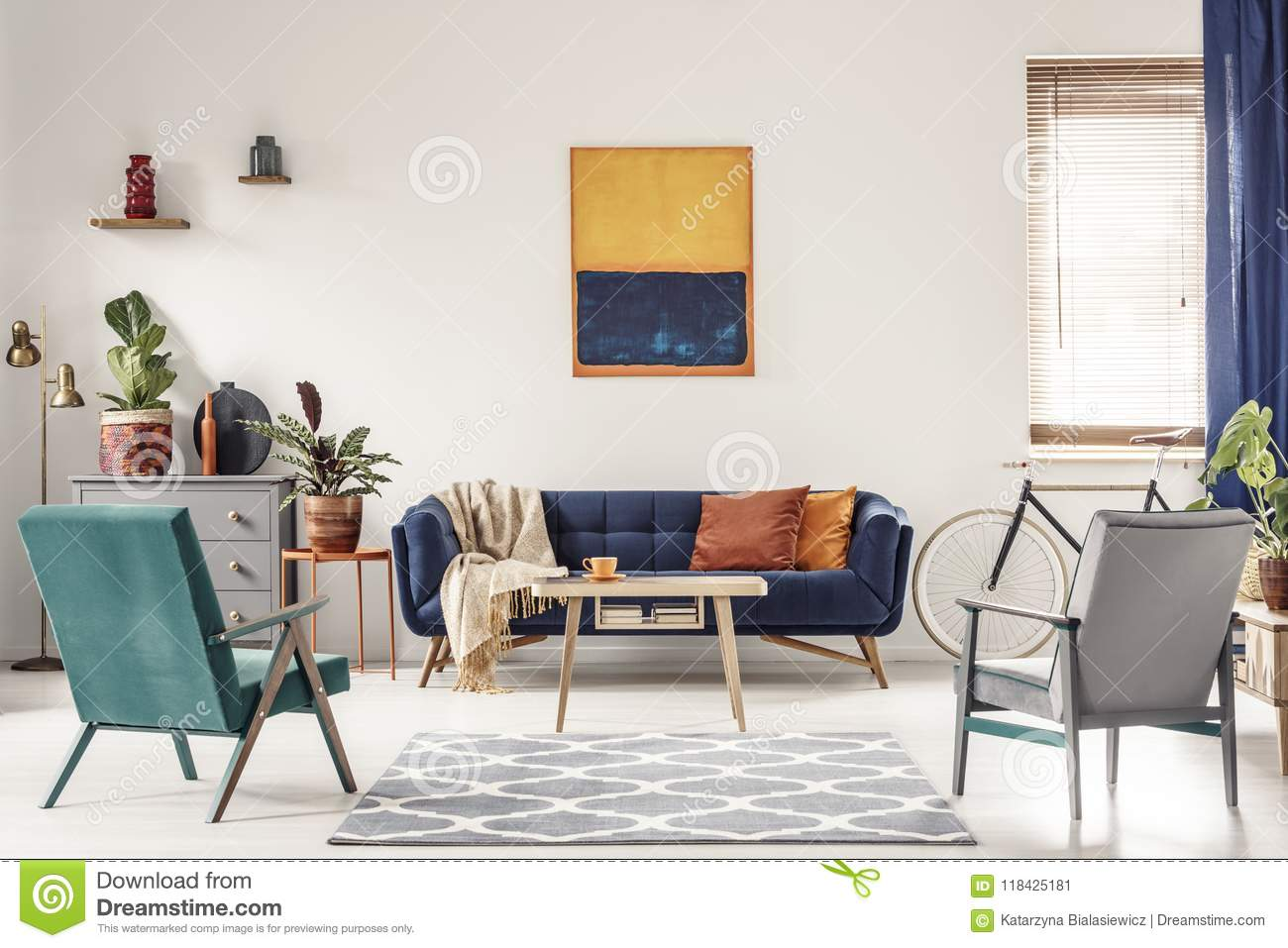 Real Photo Of A Navy Blue Sofa With Orange Cushions And An Artwo