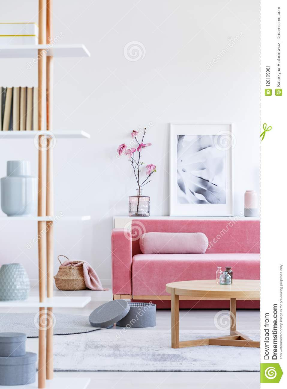 Real photo of a pink sofa with a cushion standing behind a wooden table and in front of a shelf with a poster and flowers in