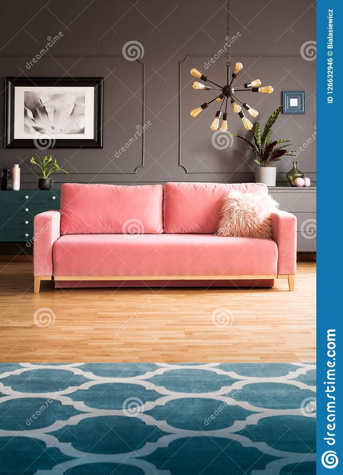 Real photo of powder pink sofa with fur cushion standing in dark