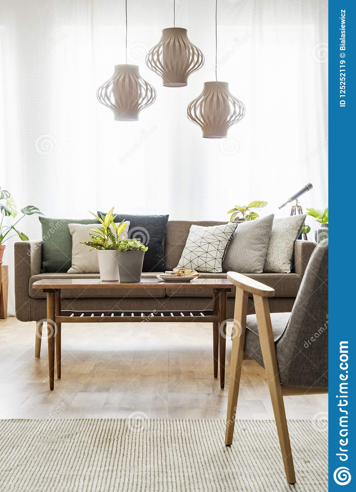 real photo of a table with plants standing between a sofa