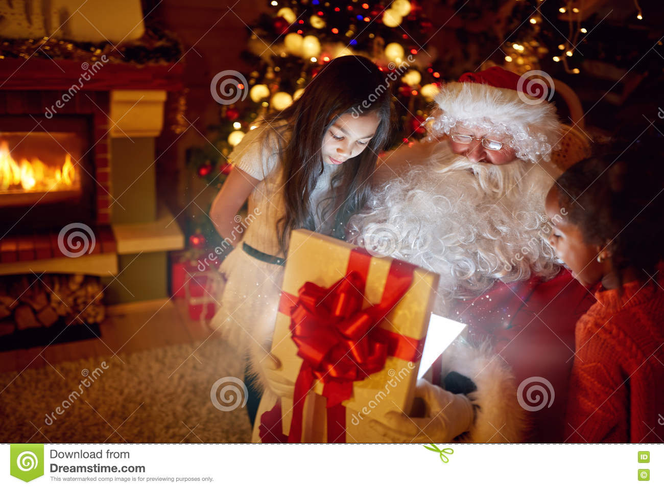 Real Santa Claus with children opening present with magical eff