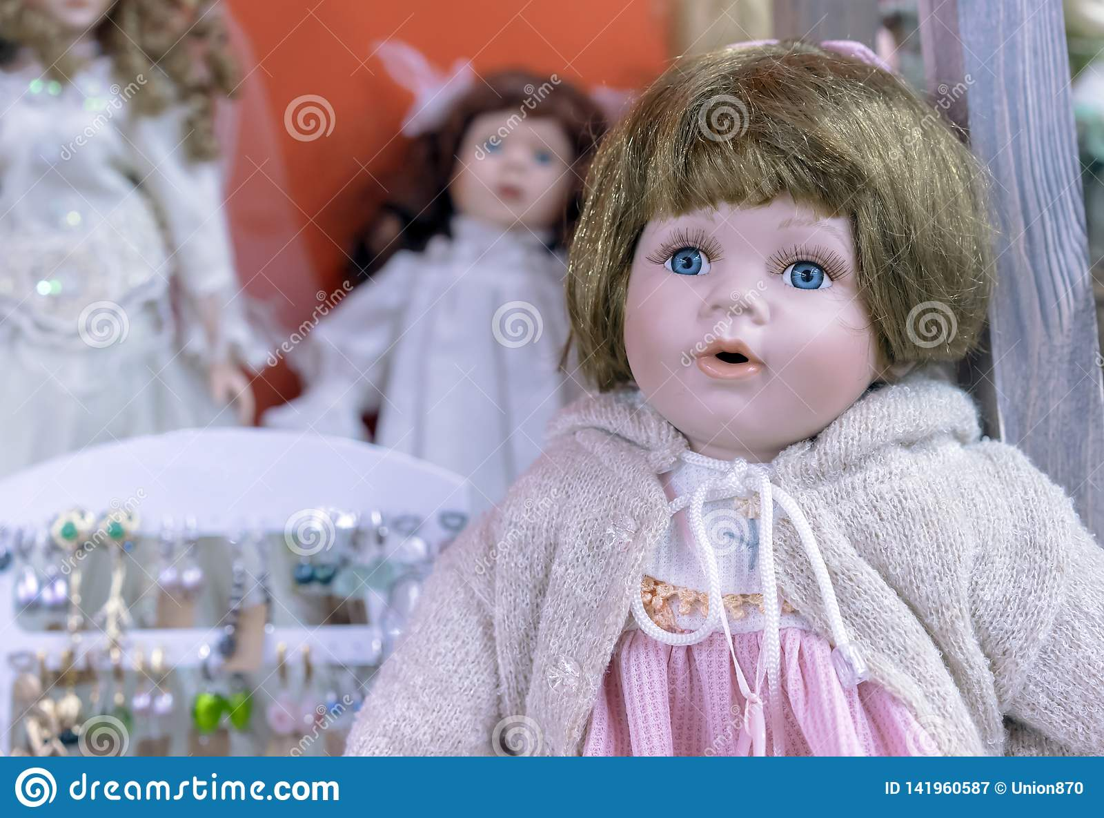 Realistiskt behandla som ett barn - dockan med blåa ögon i en beige tröja och en rosa klänning