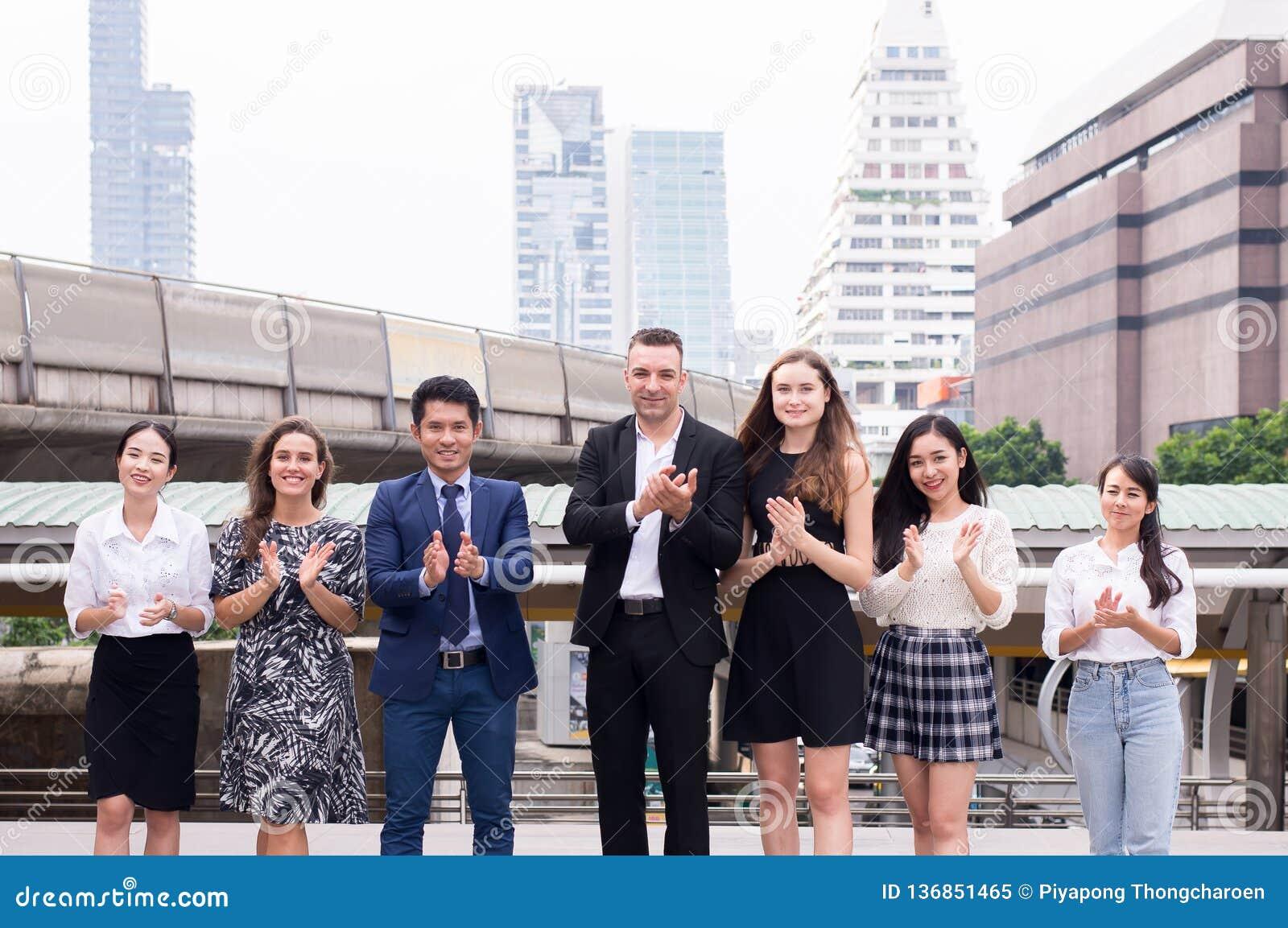 A realização do sucesso da equipe aplaude seus mãos, grupo bem sucedido de povos da diversidade do negócio, fusões e aquisição
