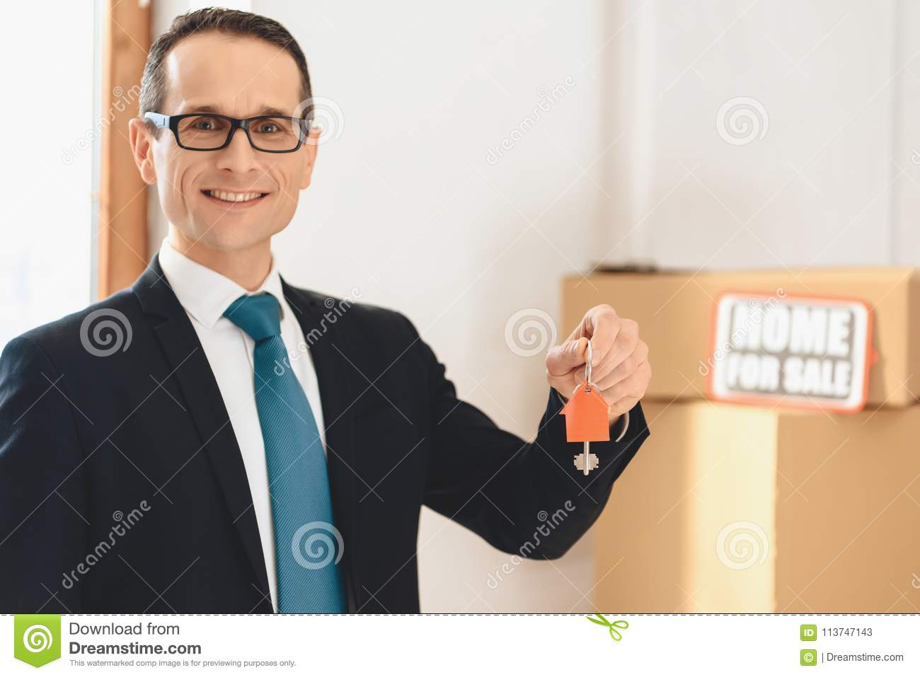 Realtor holding keys with house icon in new apartment with cardboard boxes.