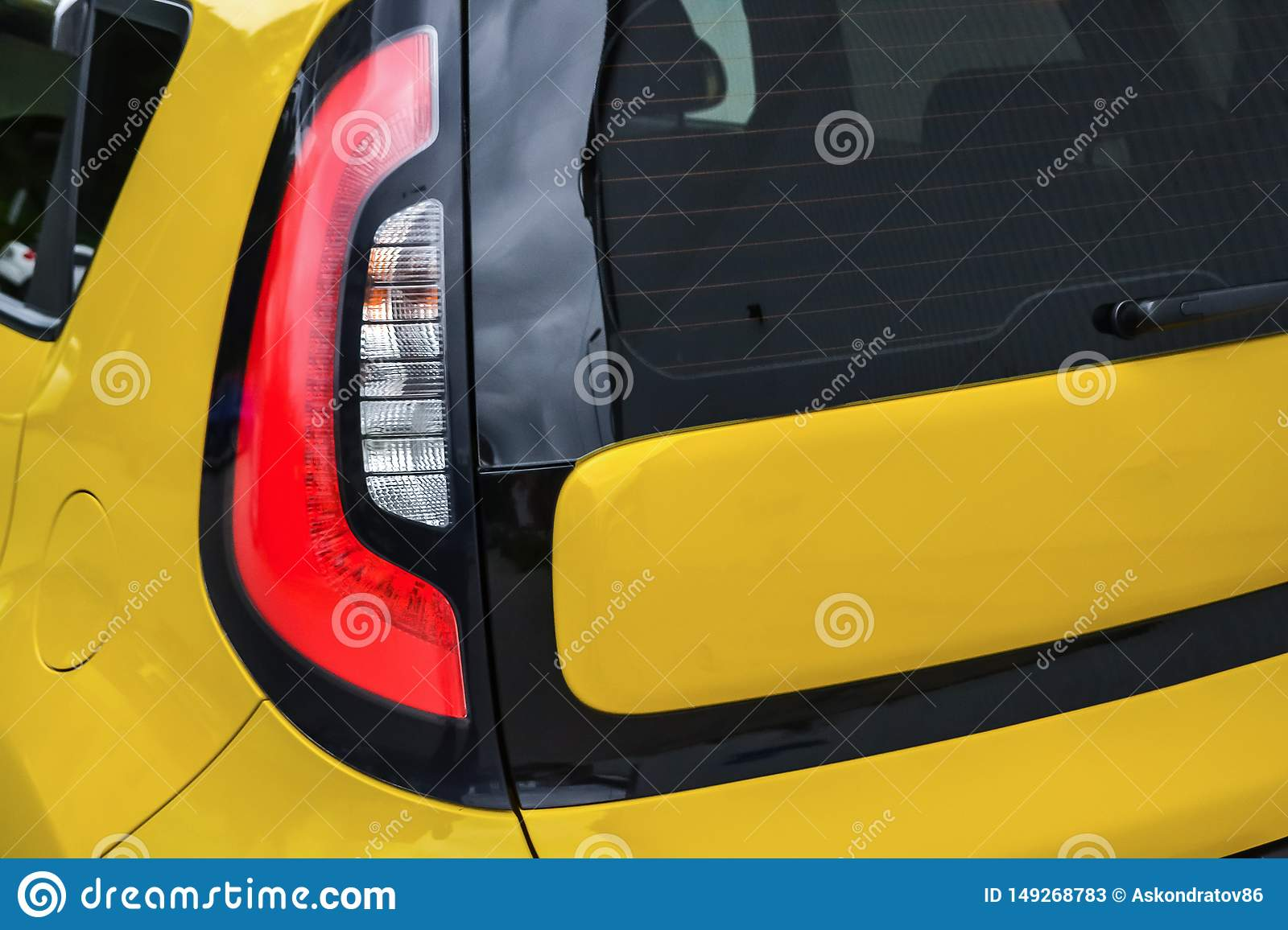 Rear taillamp view of used car in yellow color after cleaning before sale inday