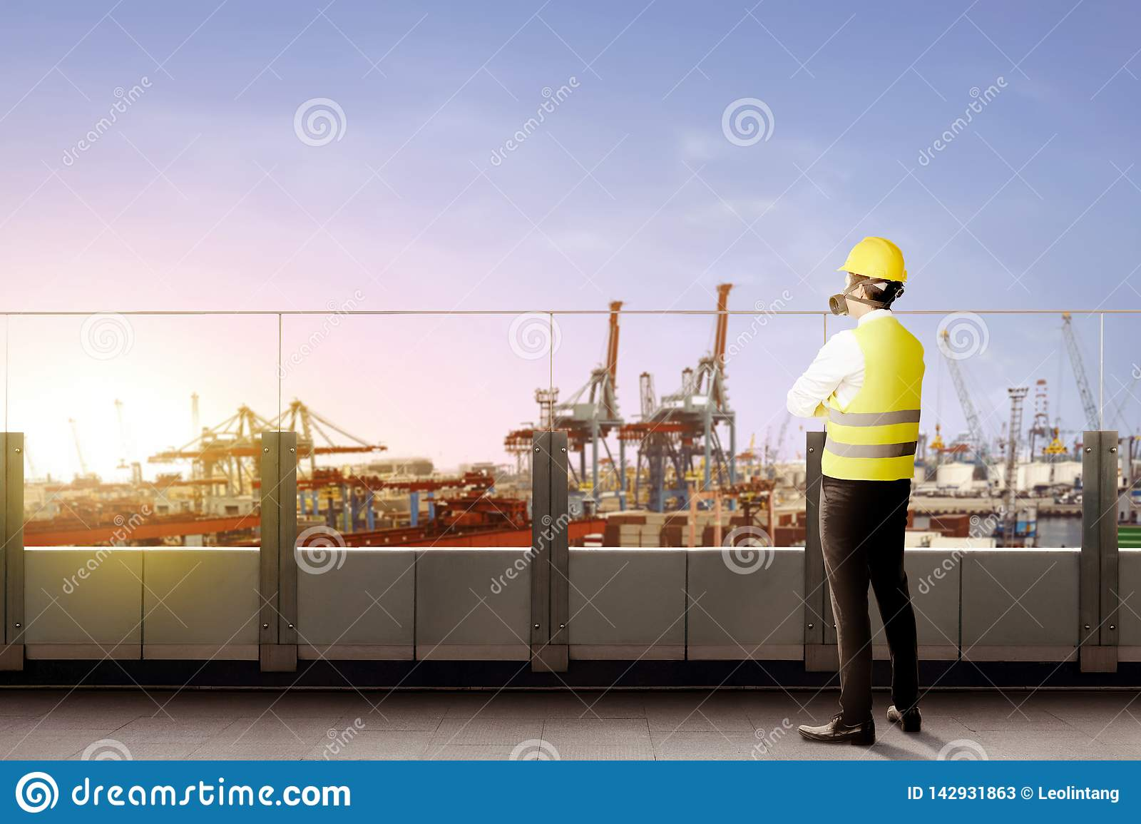Rear view of asian male worker with safety vest, hard hat and protective mask standing on office terrace and looking at dock