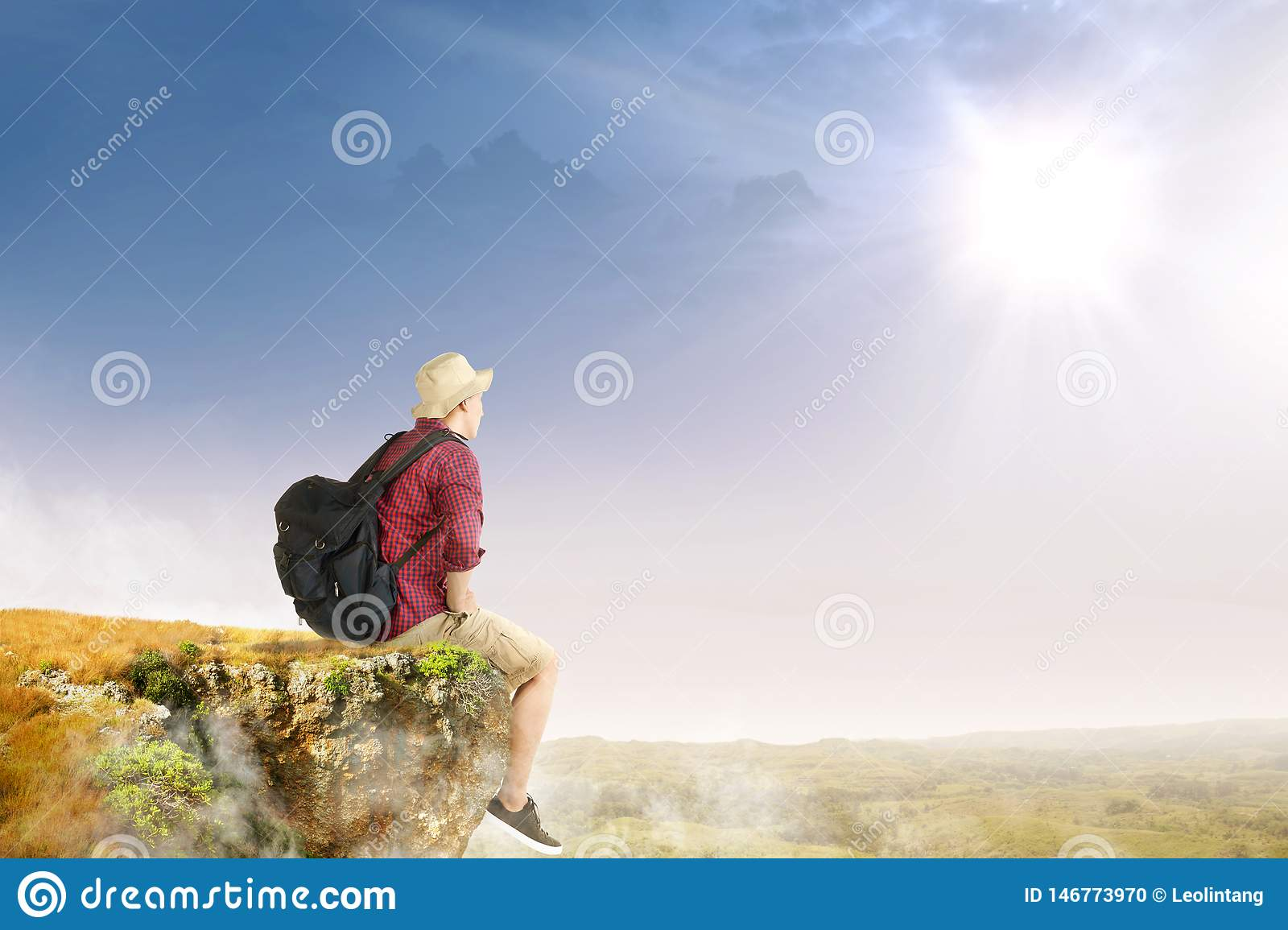 Rear view of asian traveler man with hat and backpack sitting on the edge of cliff looking at landscapes