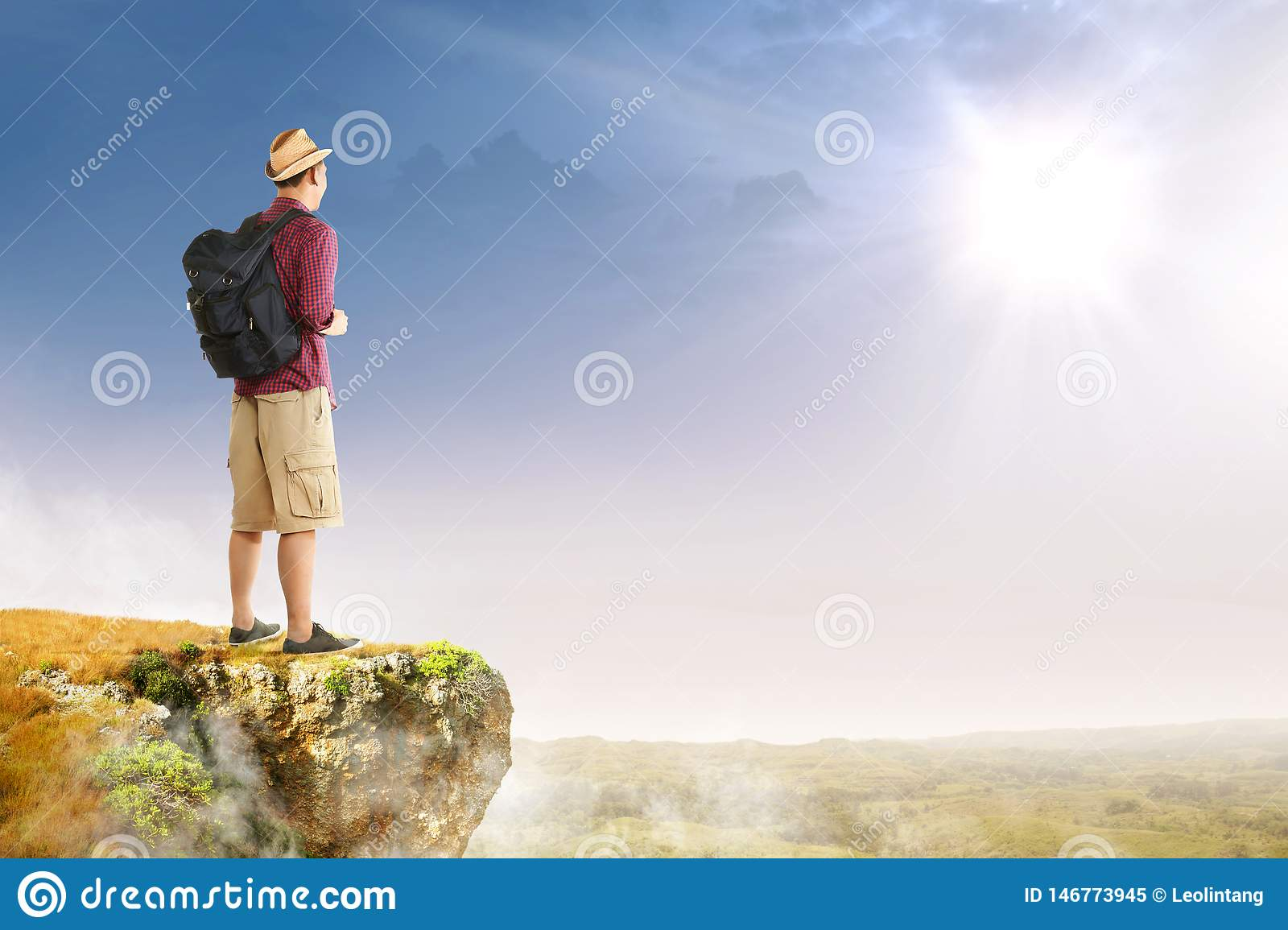 Rear view of asian traveler man with hat and backpack standing on the edge of cliff looking at landscapes