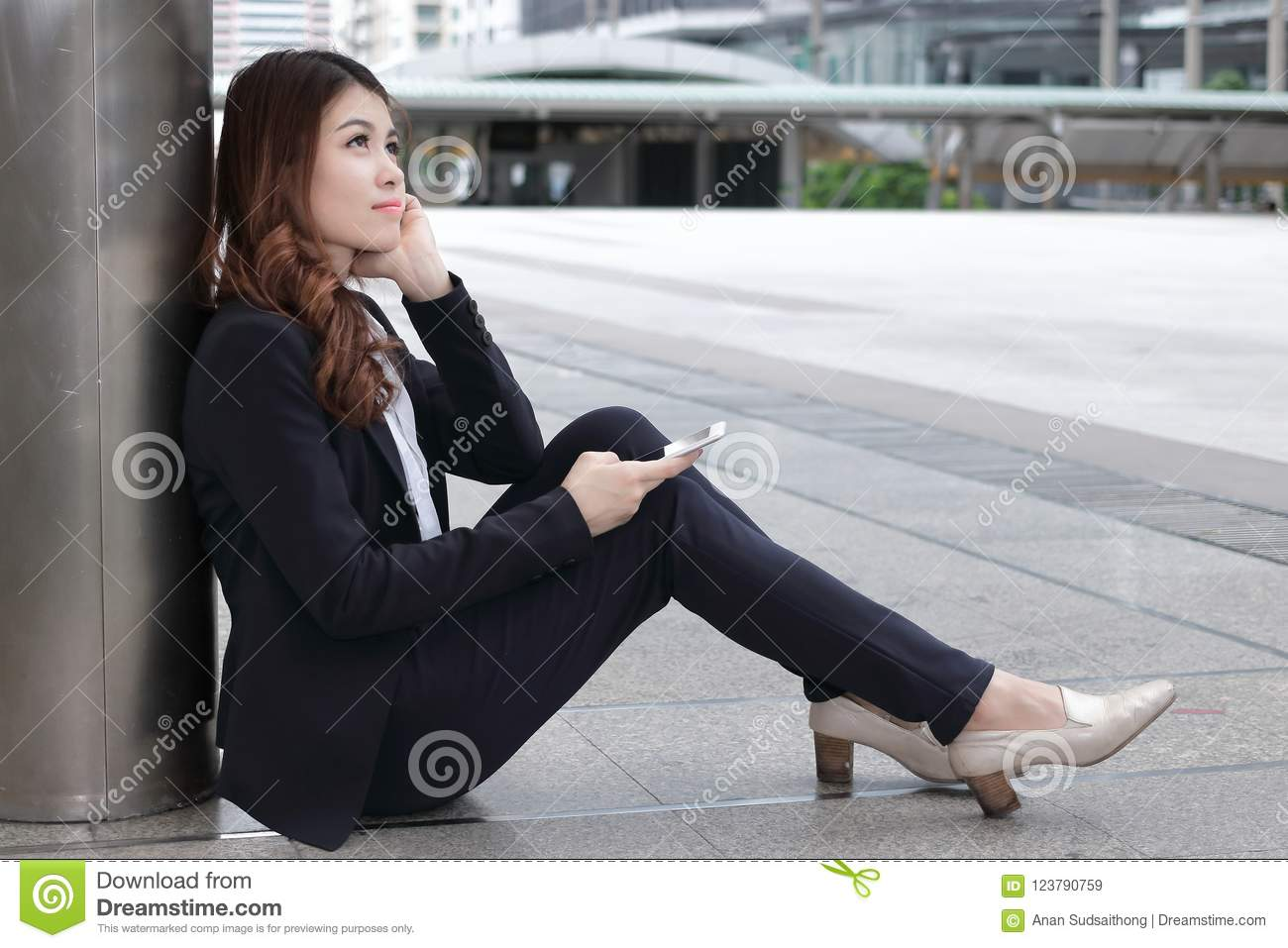 Rear view of attractive young Asian business woman in formal clothes sitting on floor and thinking about her job at urban with cop