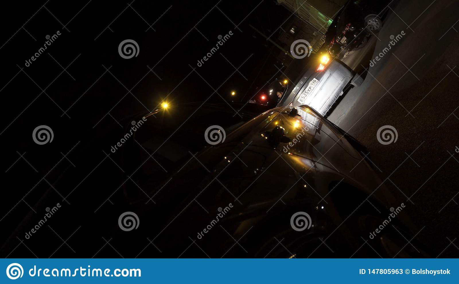 Rear view of a black car parked at night in the town street, night traffic concept. Footage. Passenger vehicle with neon
